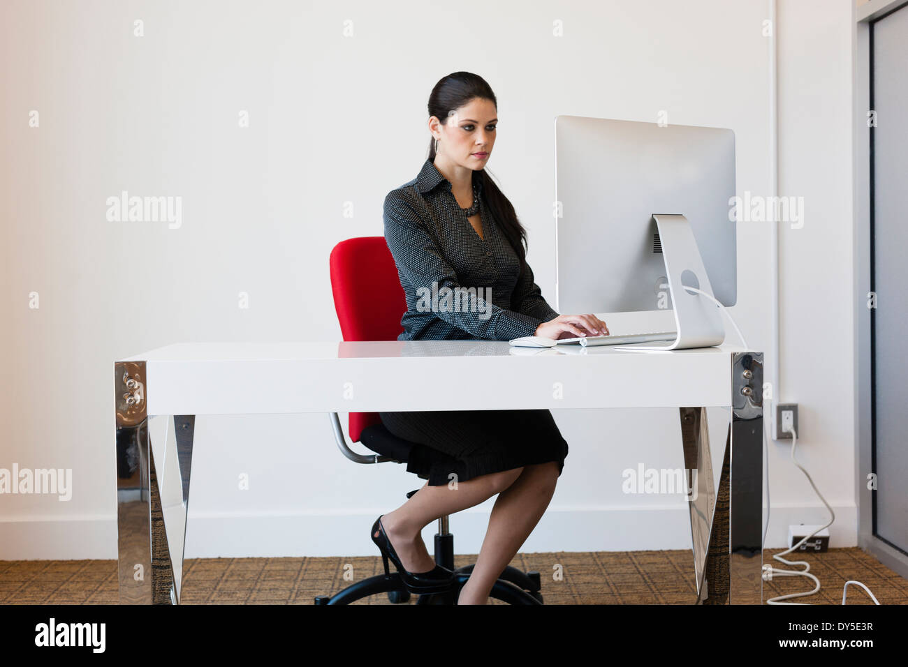 Young businesswoman sitting at desk, using computer - Stock Image