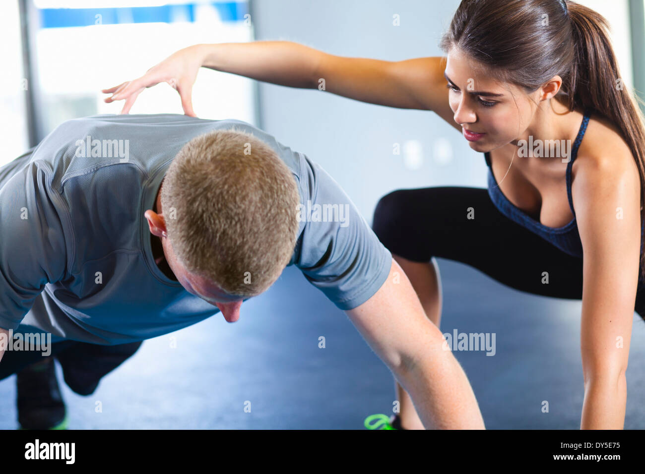 Couple helping each other in gym - Stock Image