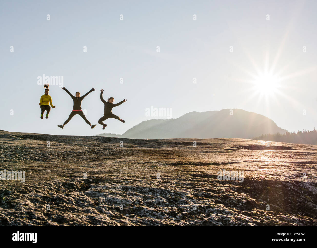 Three young female hikers jumping mid air on rock, Squamish, British Columbia, Canada - Stock Image