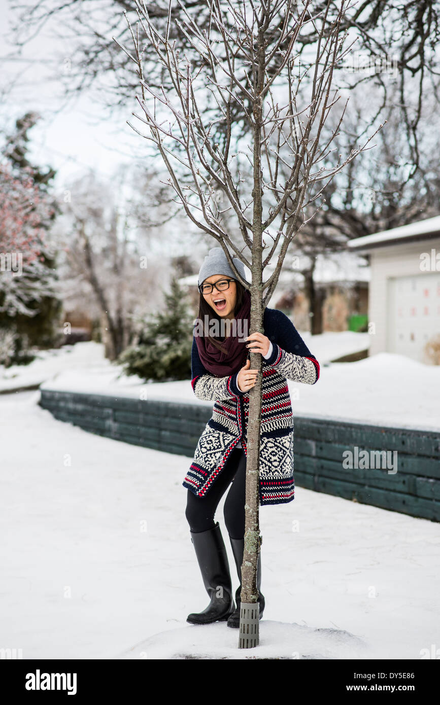 Young woman holding onto tree in slippy snow - Stock Image