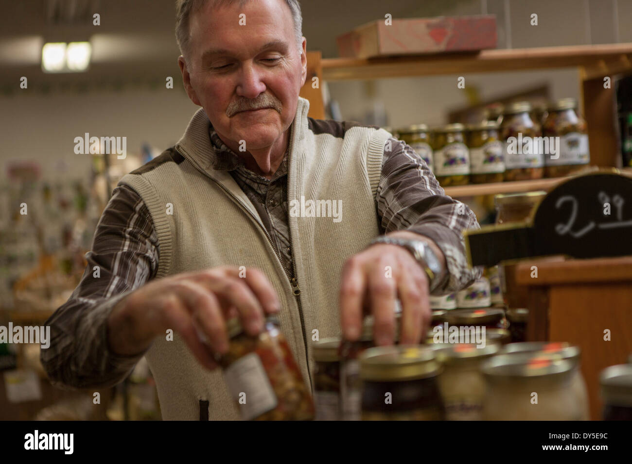Shop keeper arranging jars in shop - Stock Image
