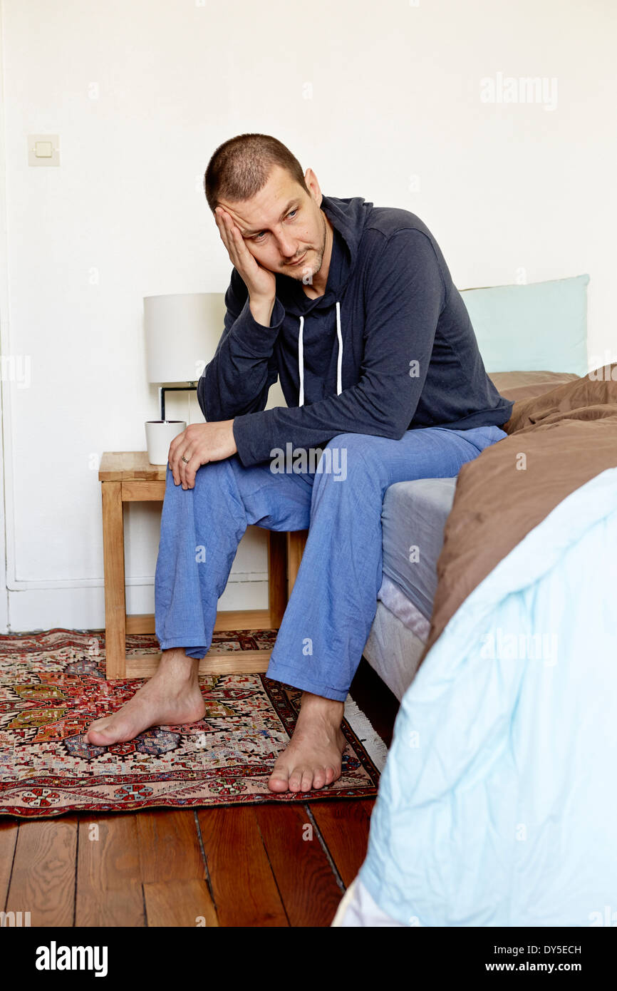 Unhappy mid adult man sitting on bed with head in hand - Stock Image