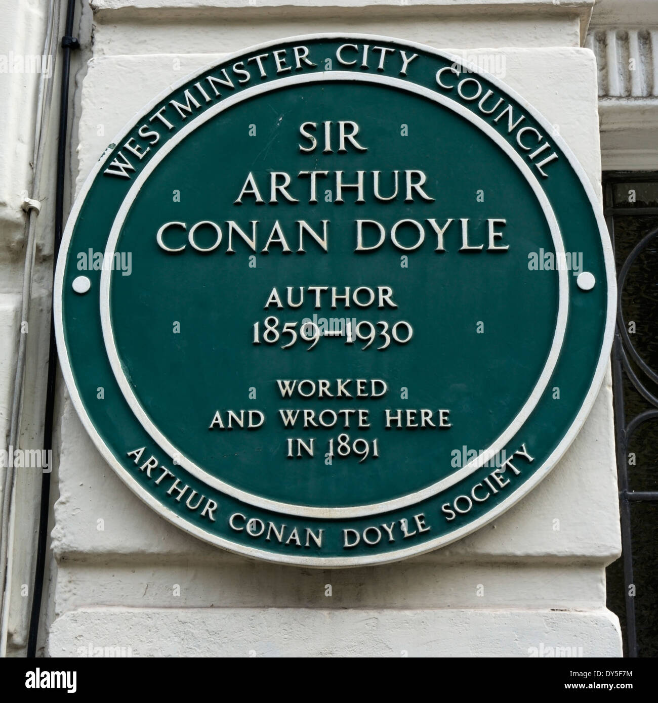 A green plaque on the property occupied by Sir Arthur Conan Doyle in Upper Wimpole Street, London. - Stock Image