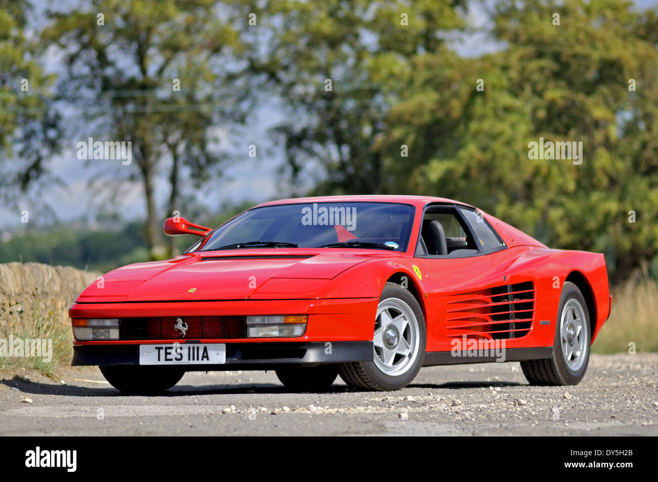 Ferrari Testarossa standing on a country lane in the Summer with trees in the background - Stock Image