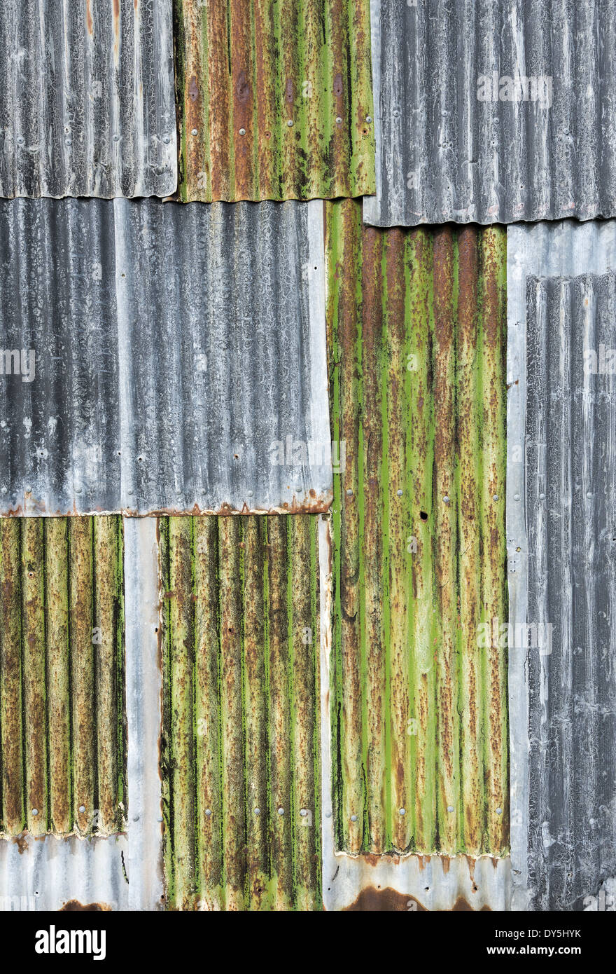 Rusty weathered metal sheeting layers on barn exterior - Stock Image
