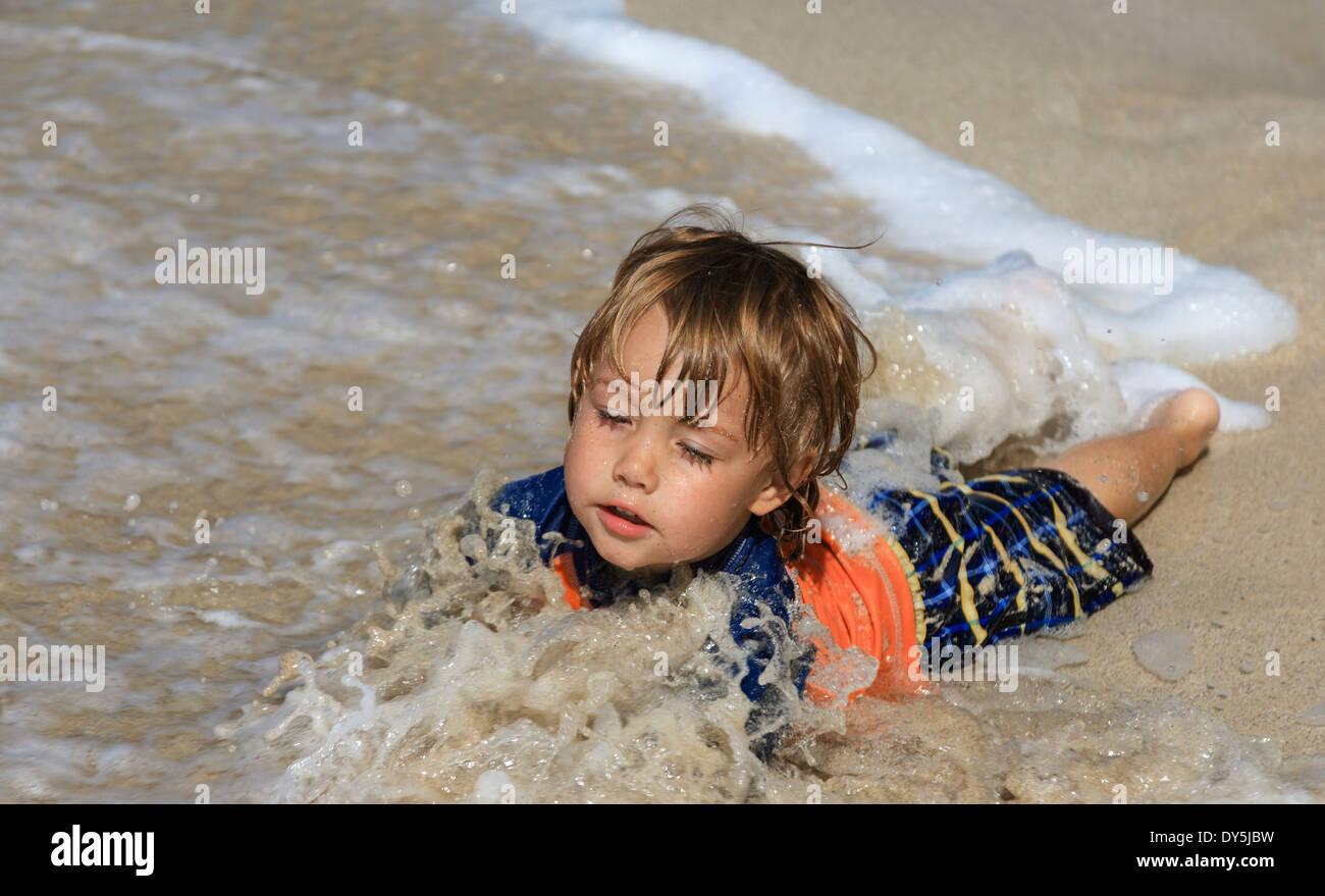 Young boy enjoys ocean at Laaloa Beach Park on the Big Island of Hawaii - Stock Image