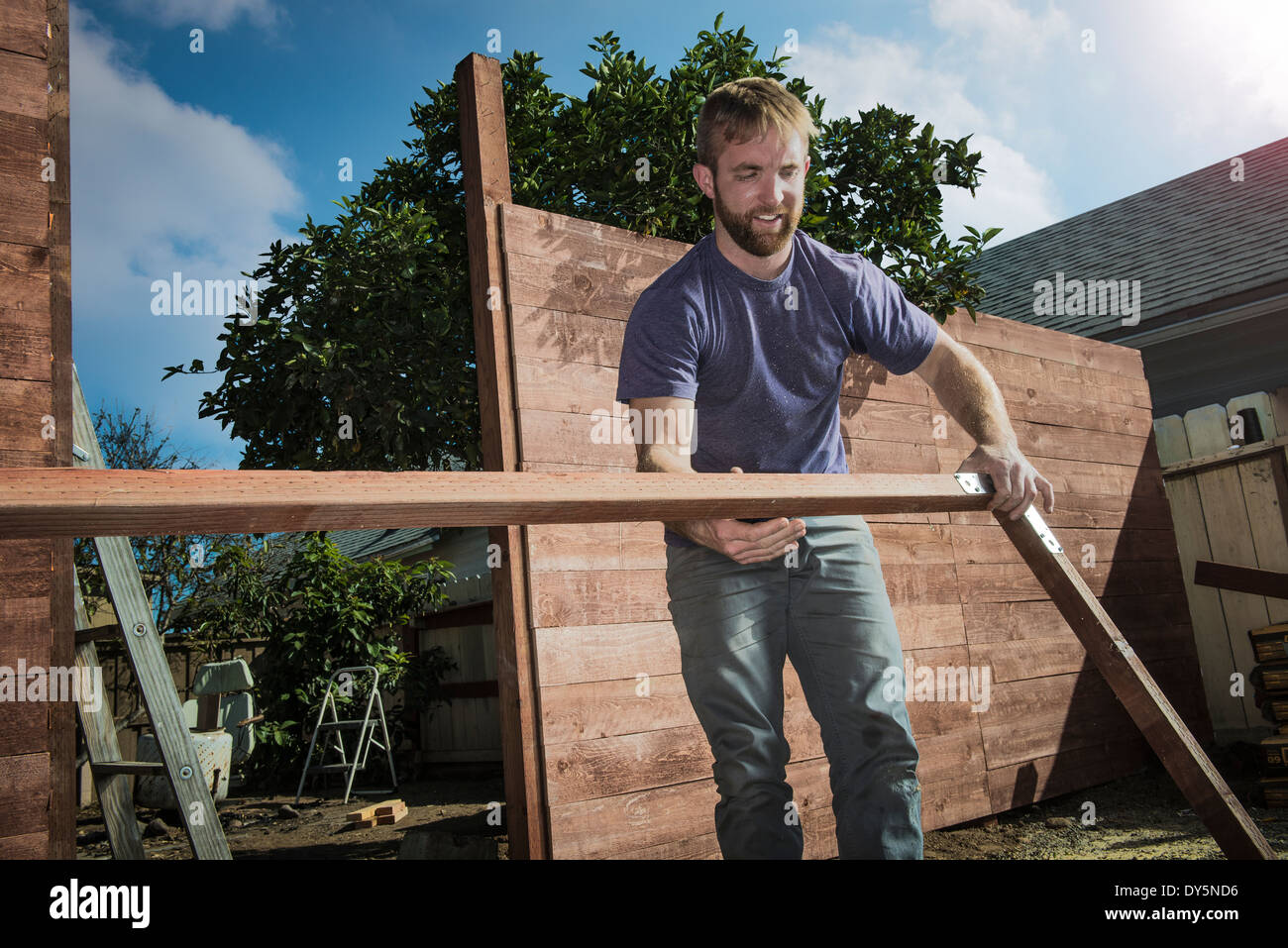 Joiner in backyard lifting wood framework Stock Photo