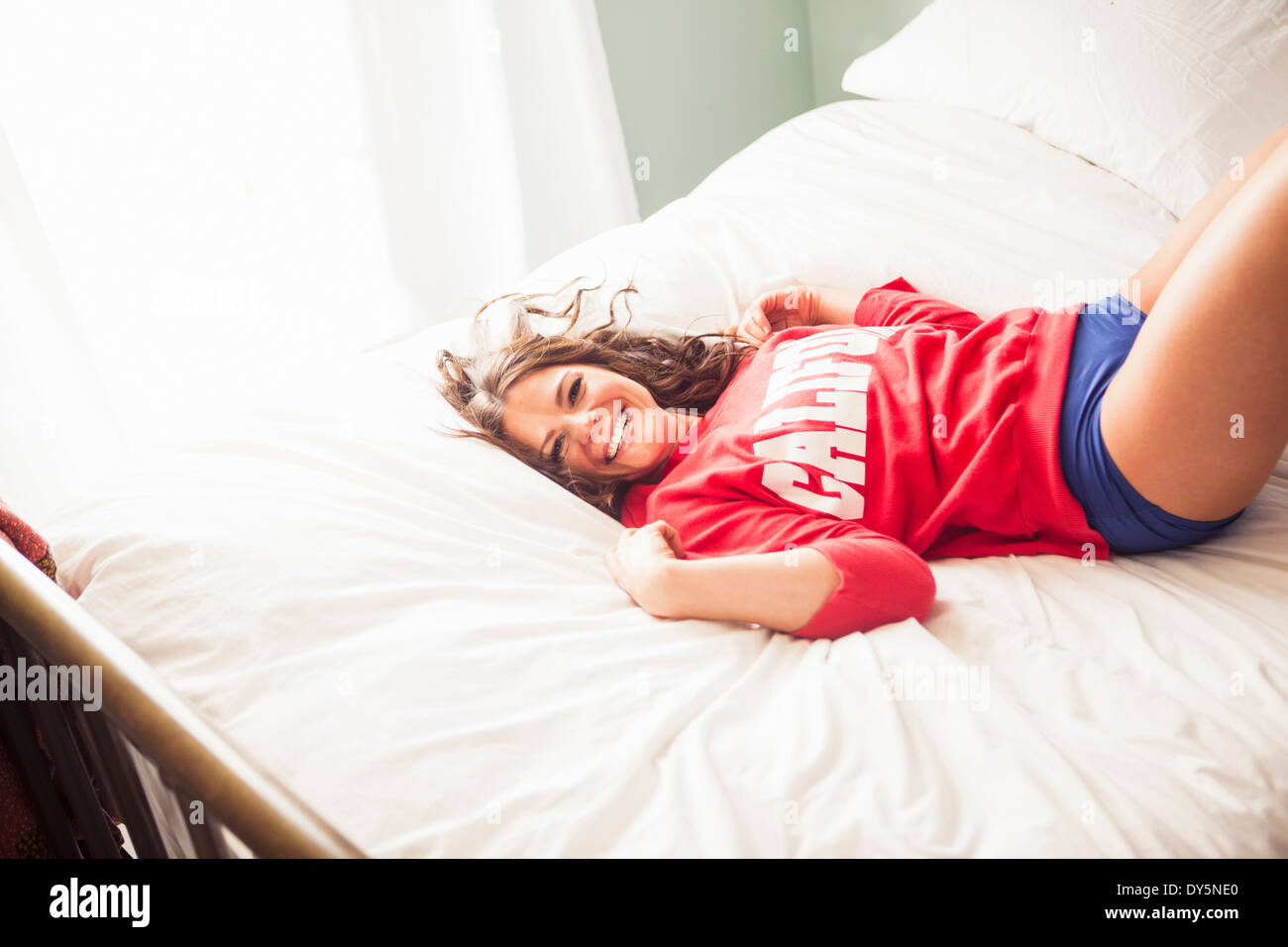 Young woman lying on bed - Stock Image