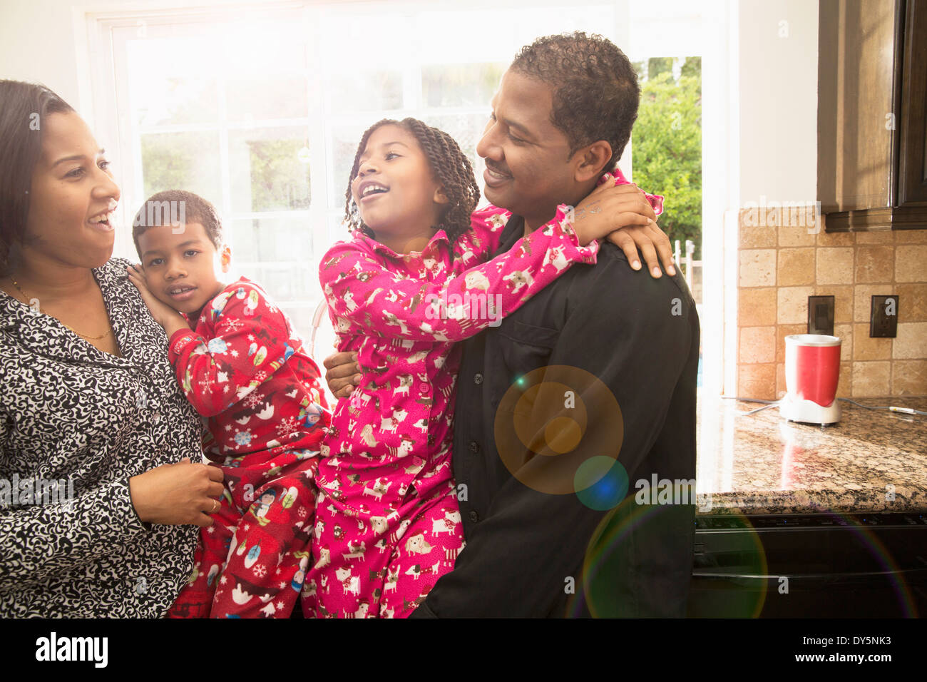 Mid adult couple and children in kitchen - Stock Image
