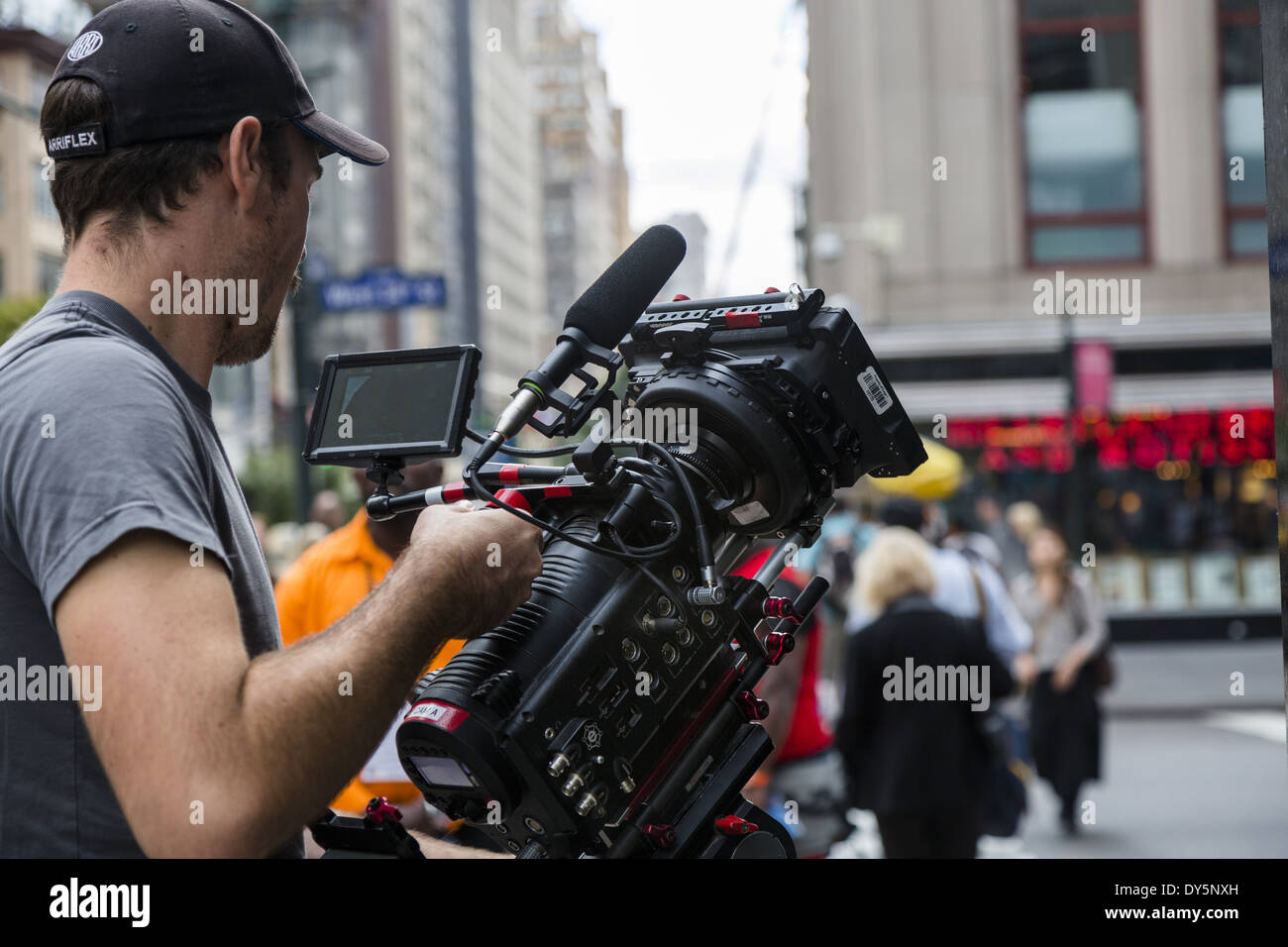 Cameraman working in the streets of New York with a Red One video camera - Stock Image