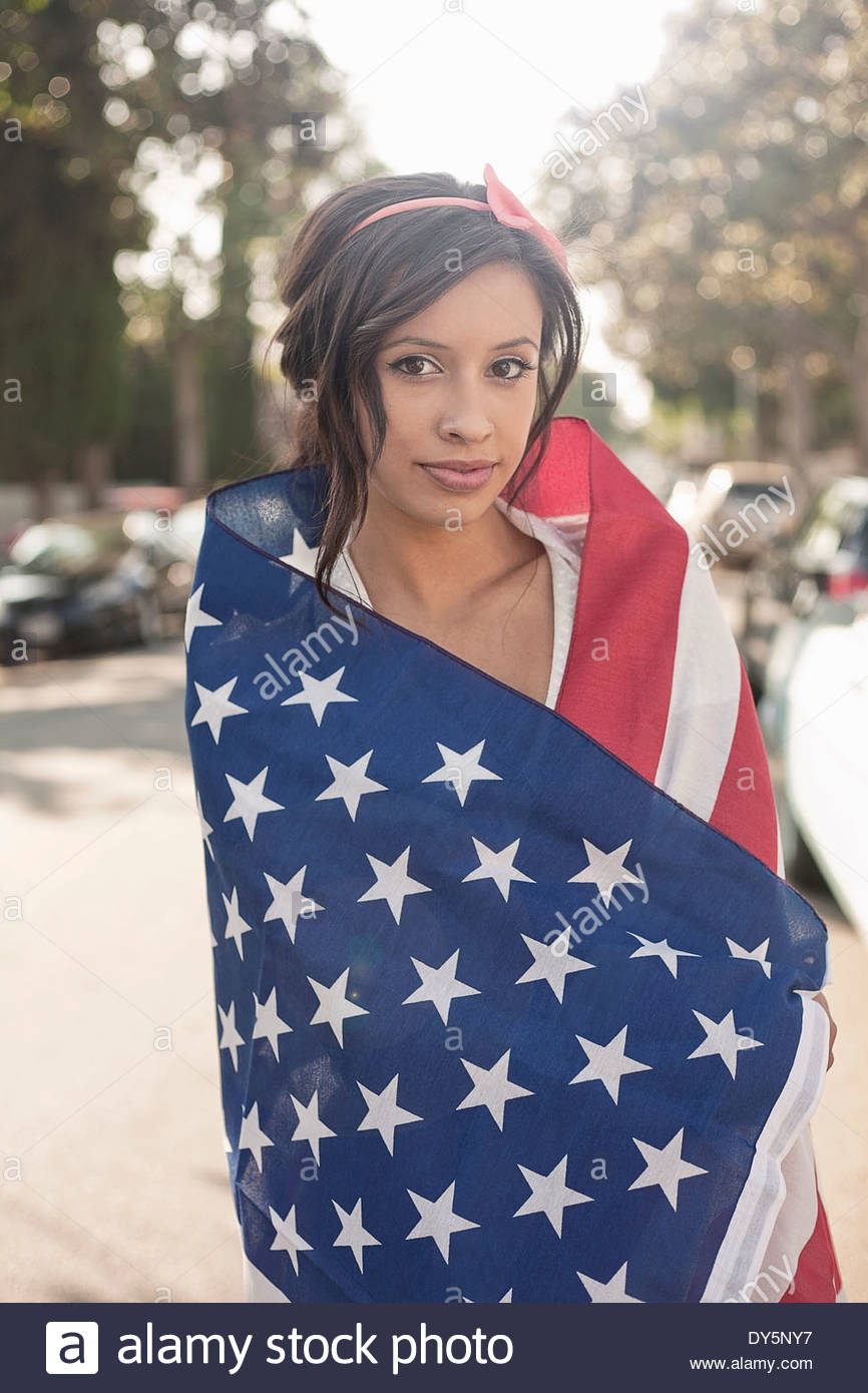 Portrait of young woman standing on street wrapped in American flag - Stock Image