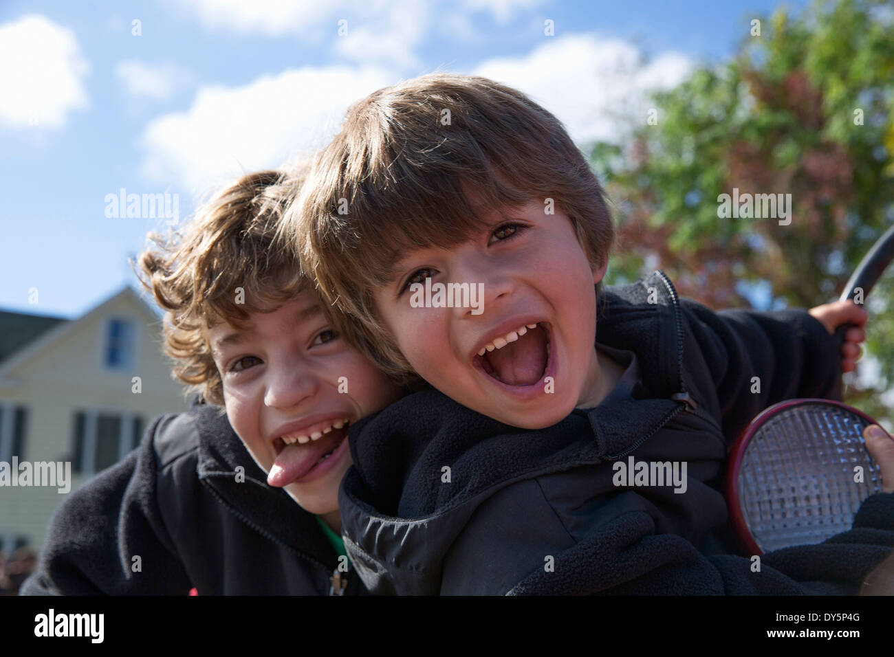 Two brothers sticking out tongues and fooling around - Stock Image
