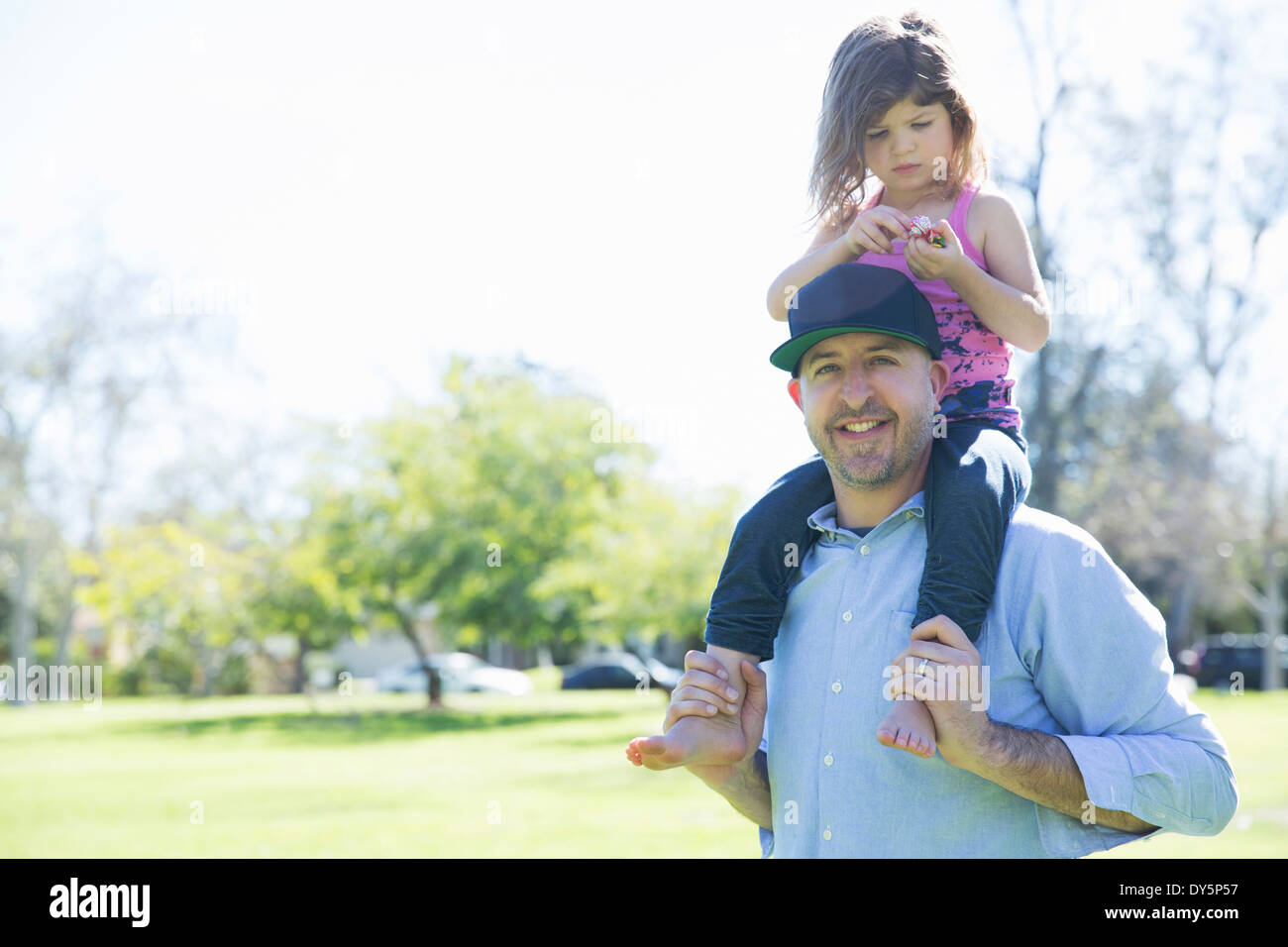 Portrait of mid adult man with young daughter on his shoulders Stock Photo