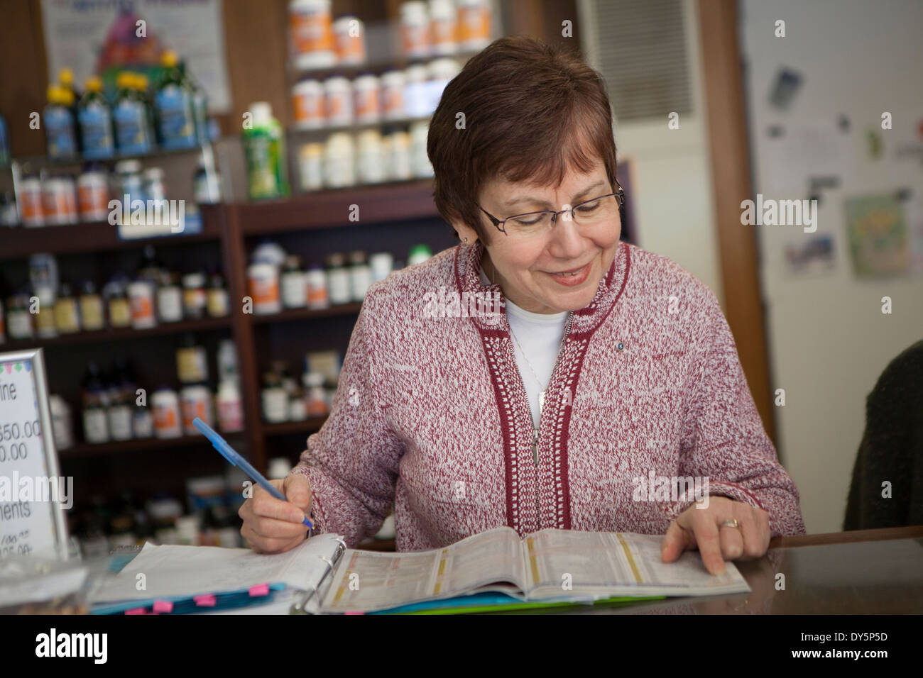 Health foods store owner doing paperwork Stock Photo