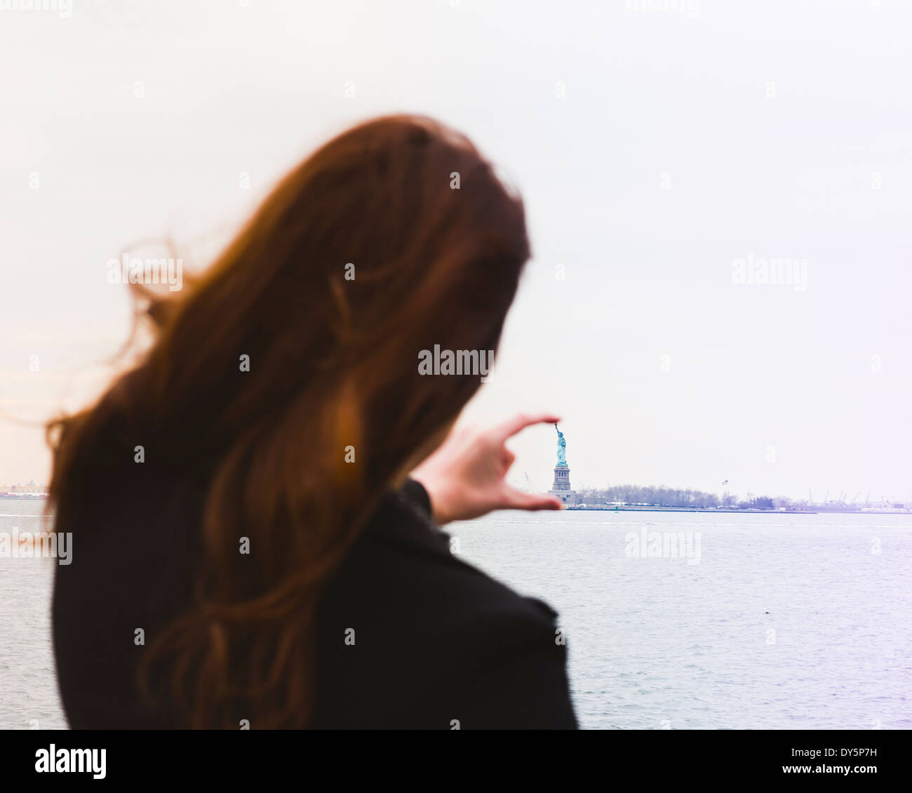 Young woman aligning fingers with statue of liberty, New York, USA - Stock Image