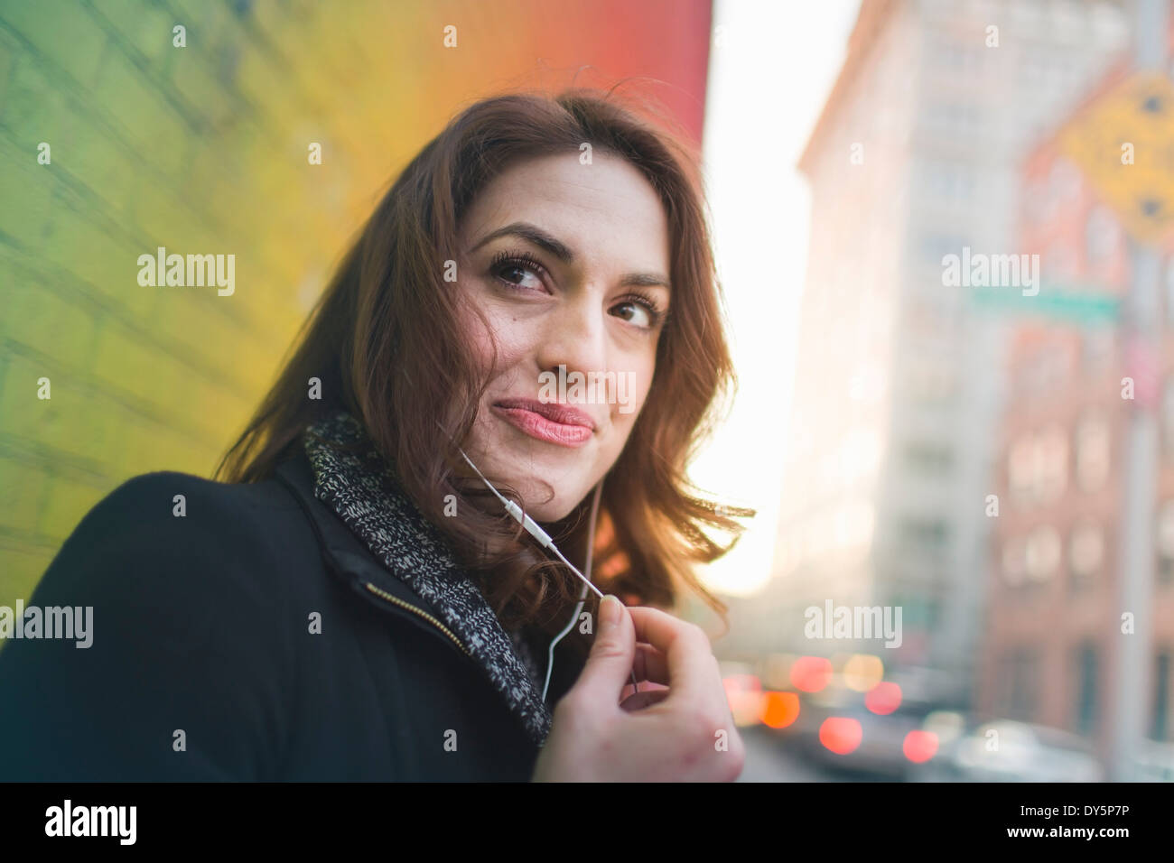 Young woman listening to earphones on city street - Stock Image