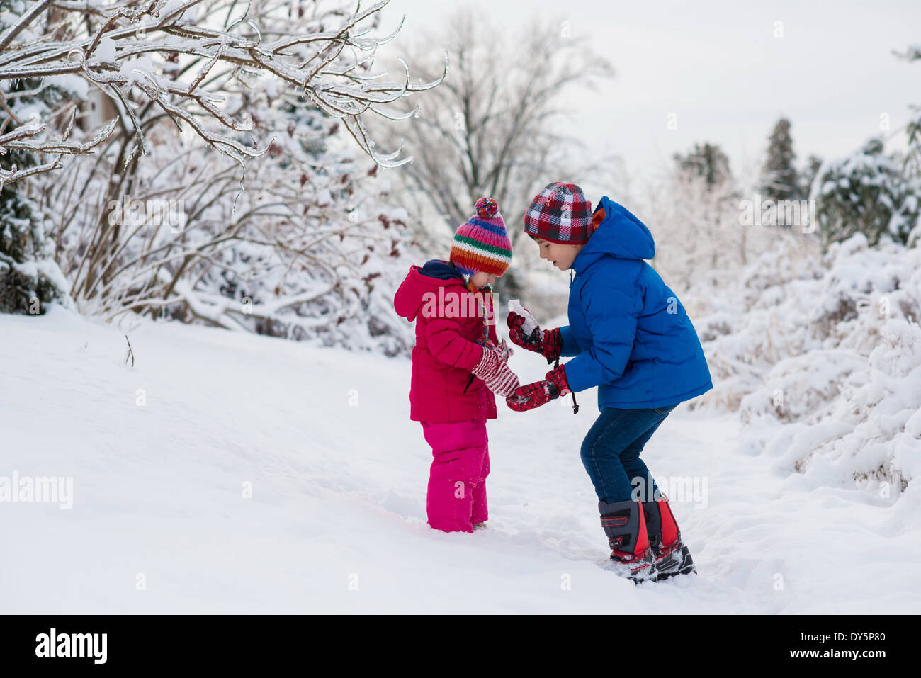 Brother showing icicles to sister whilst out in snow - Stock Image
