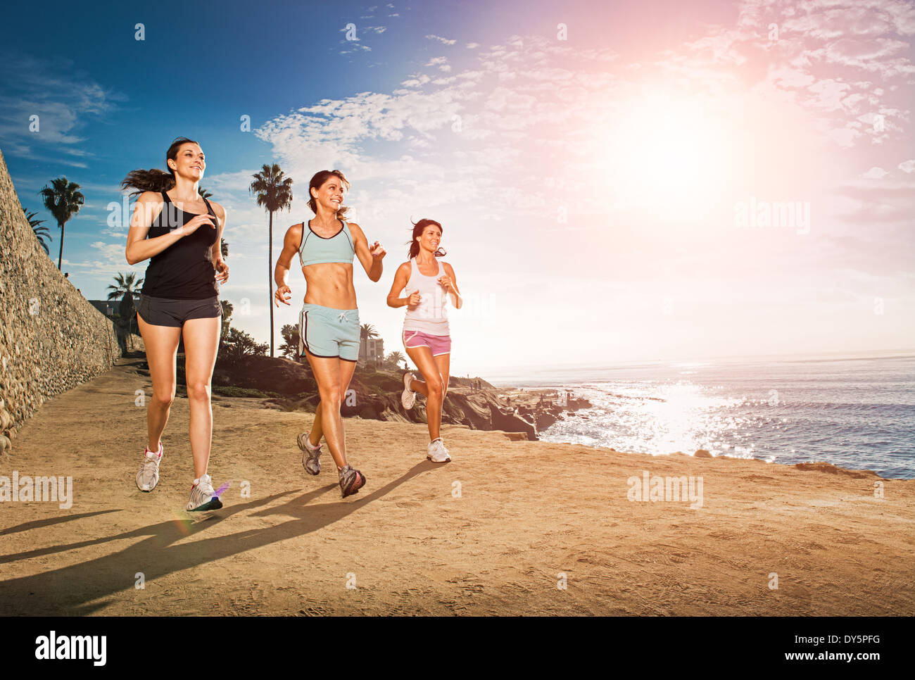 Mid adult women jogging along cliff - Stock Image