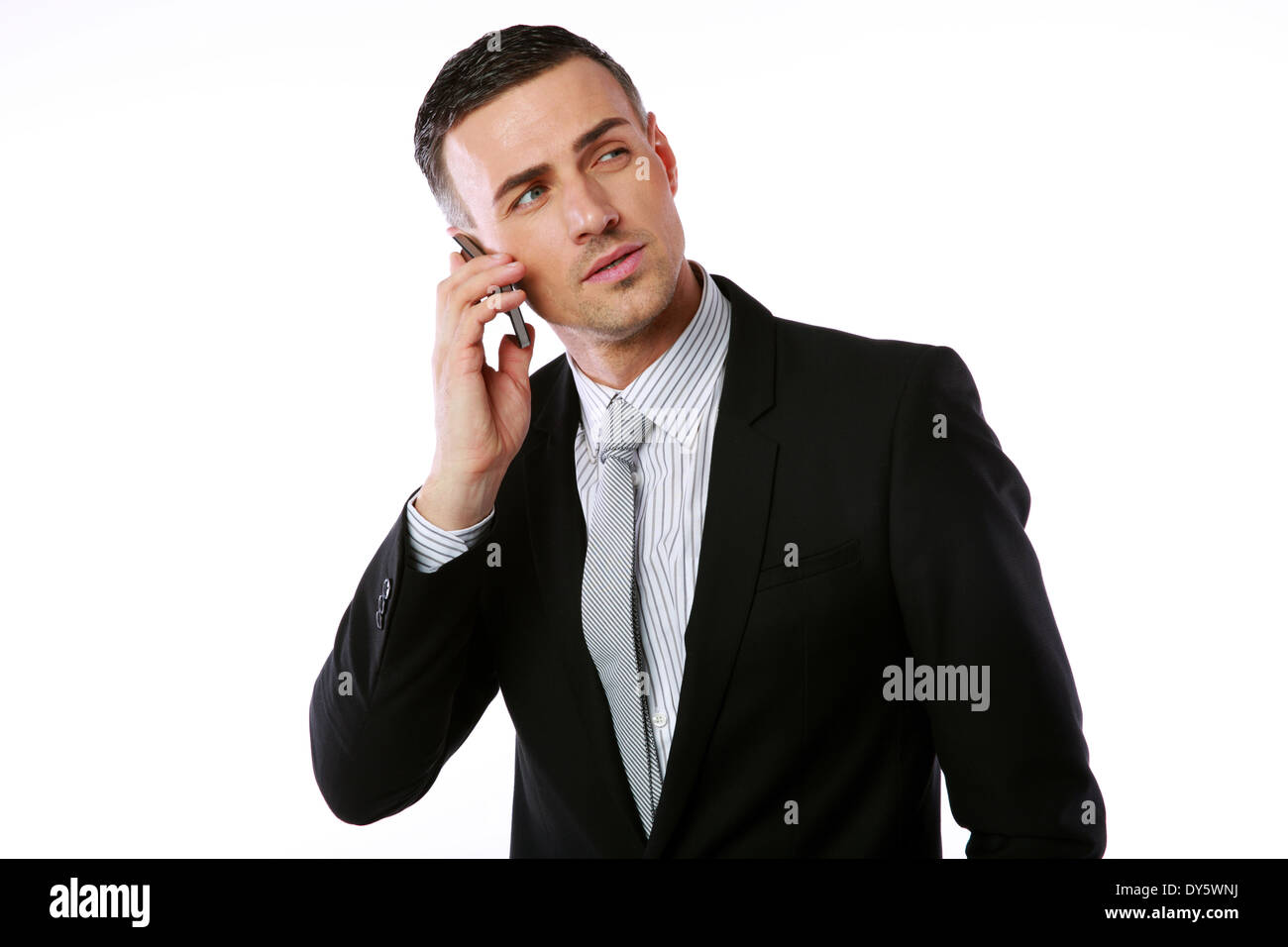 Confident businessman talking on the phone over white background - Stock Image