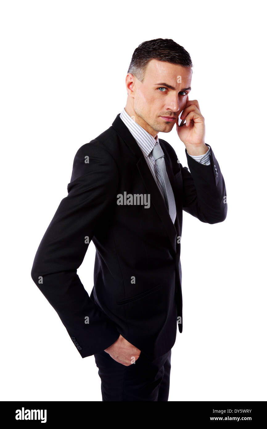 Handsome businessman talking on his mobile phone over white background - Stock Image