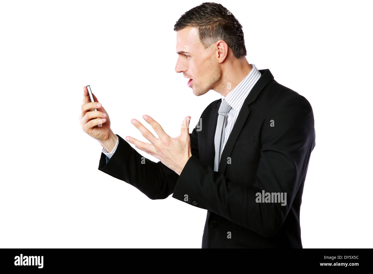 Angry businessman yelling on his cell phone over white background - Stock Image