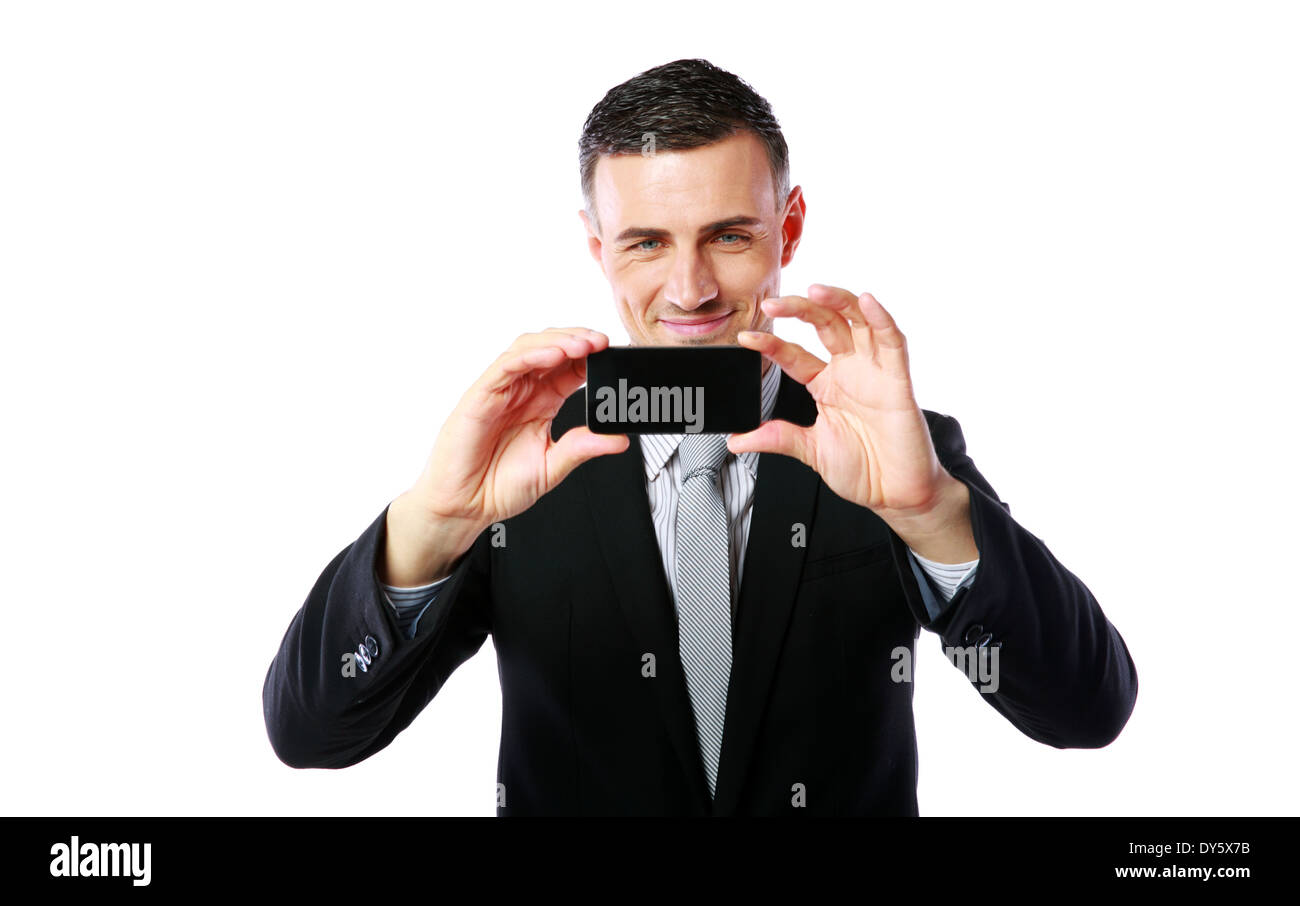 Happy businessman making photo with his cellphone over white background - Stock Image