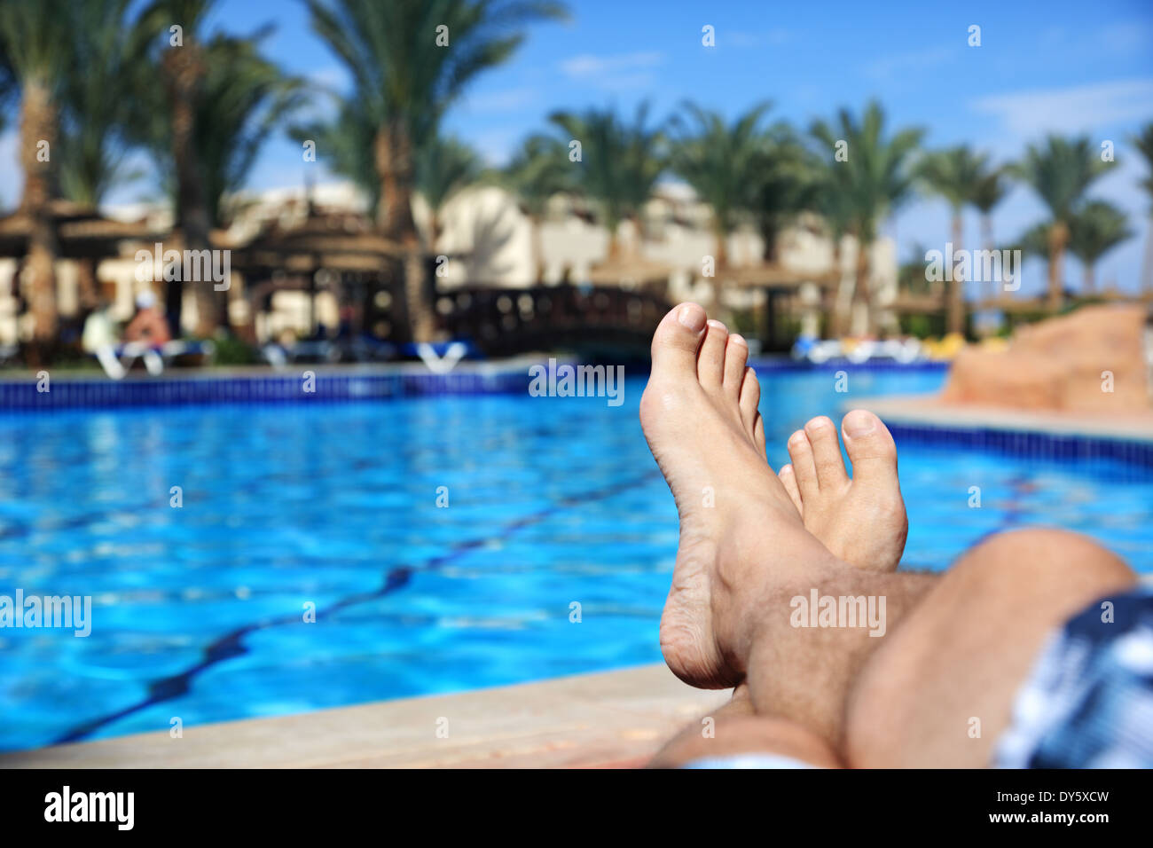 Sunbathing by swimming pool - Stock Image