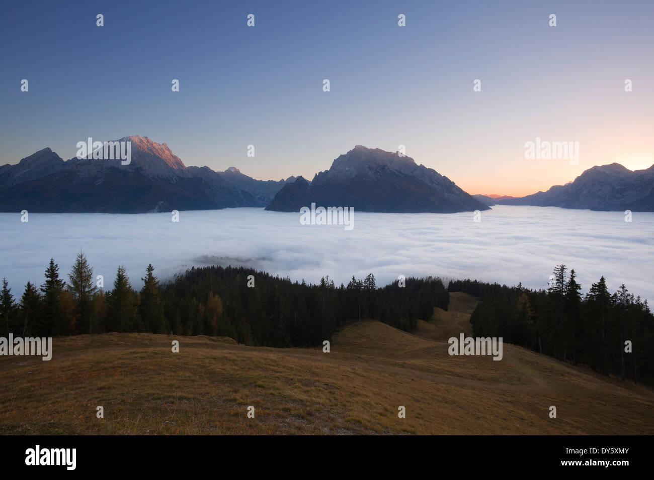 View over the fog in the valley onto Watzmann, Hochkalter and Reiteralpe at dawn, Berchtesgaden region, Berchtesgaden National P - Stock Image