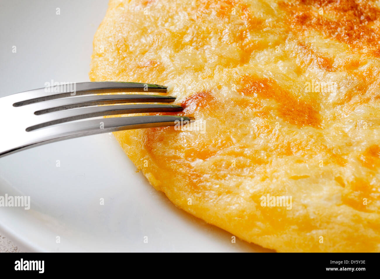 closeup of a plate with a typical tortilla de patatas, spanish omelet, on a set table - Stock Image