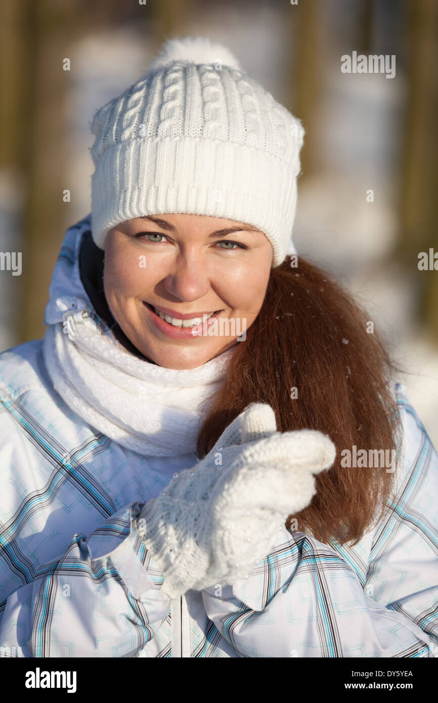 Woman portrait in winter clothes in sunlight - Stock Image