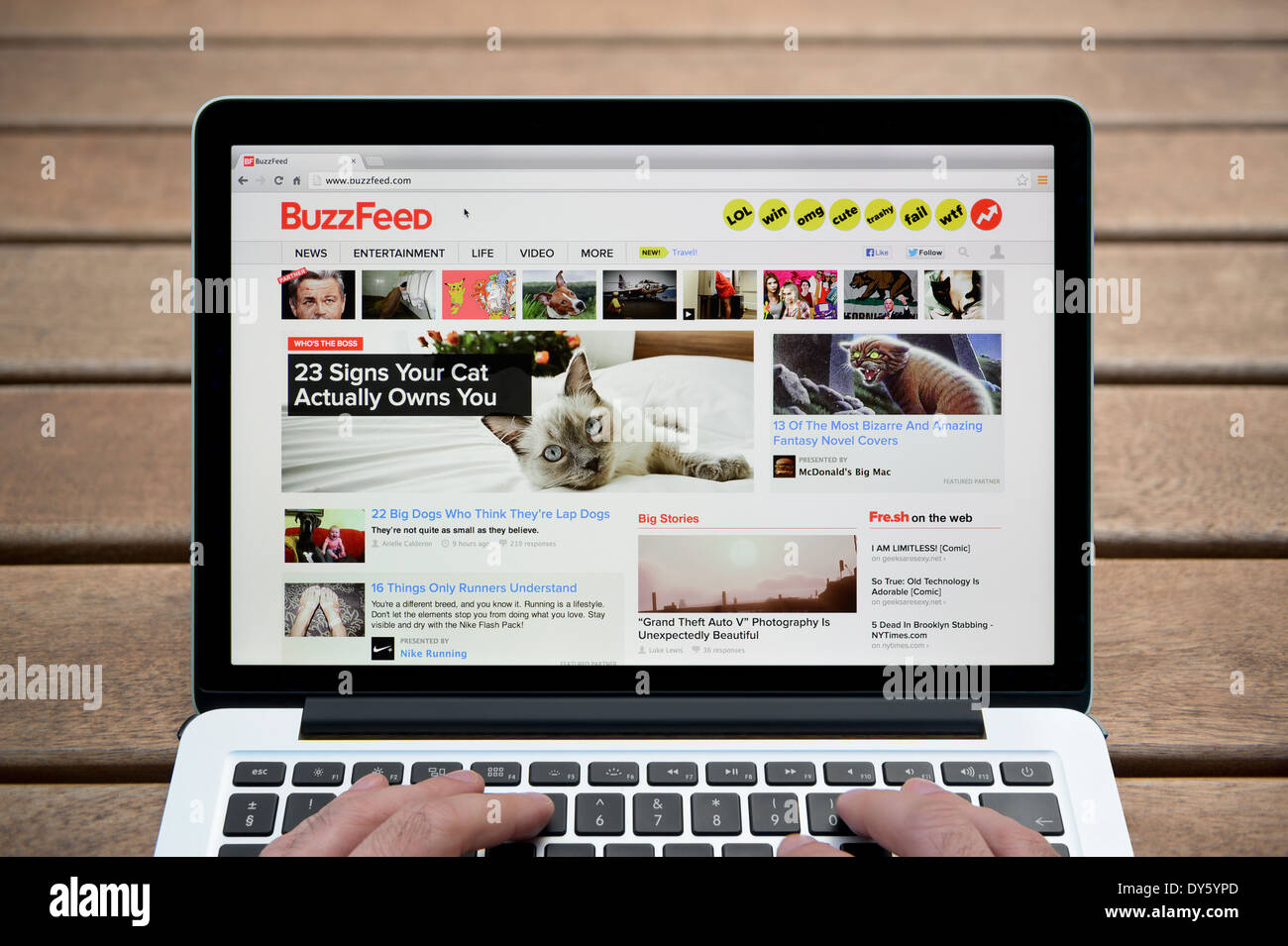 The BuzzFeed Website On MacBook Against A Wooden Bench Outdoor Background Including Mans Fingers