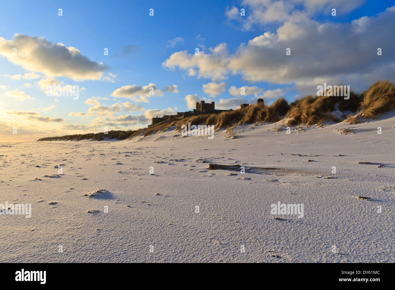Fresh Spring snow at dawn highlight ripples and marks in the sand beneath Bamburgh Castle,  Bamburgh, Northumberland, England - Stock Image