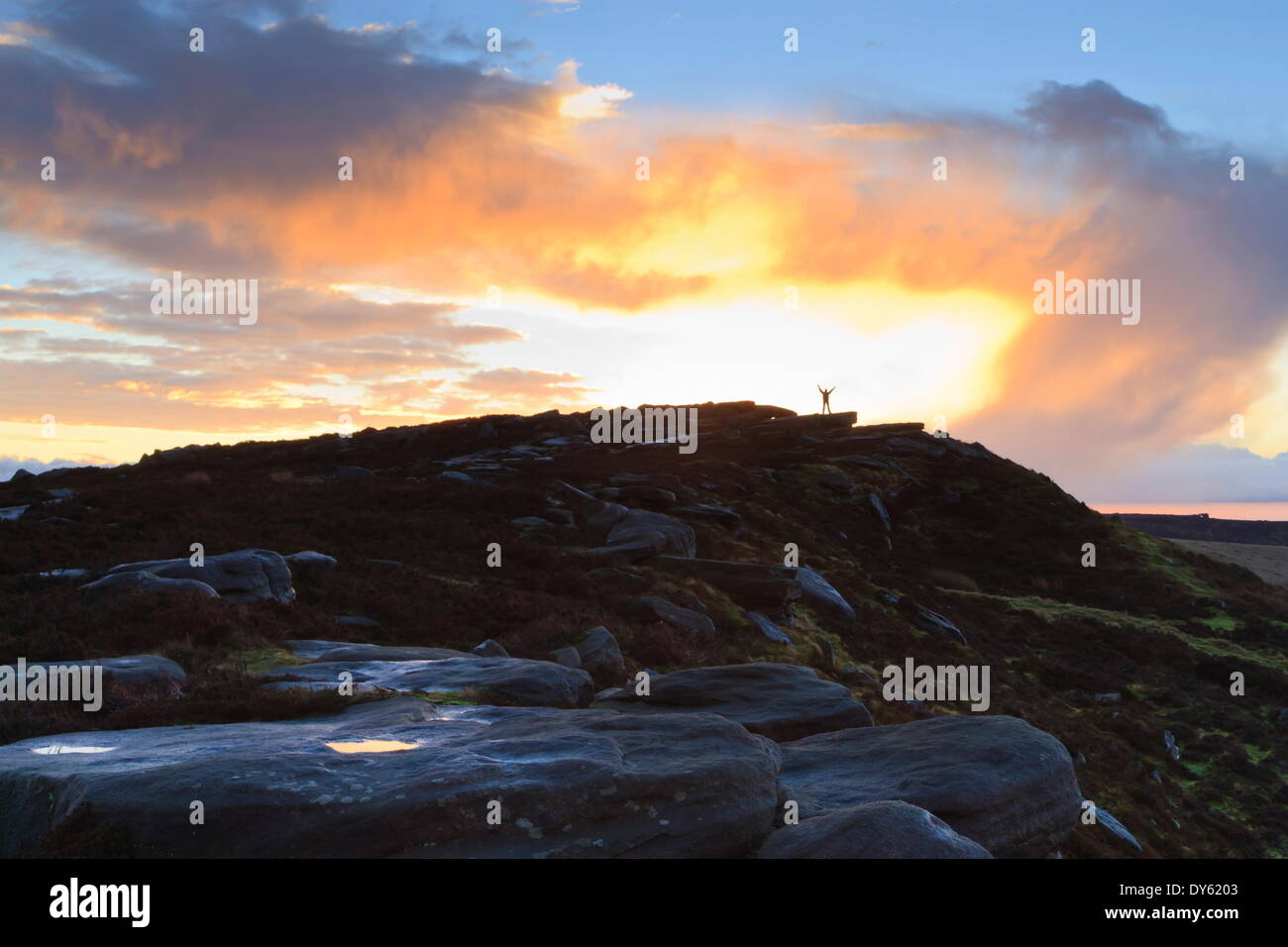 Person on rocks of Stanage Edge with winter sunrise, near Hathersage, Peak District National Park, Derbyshire, England, - Stock Image