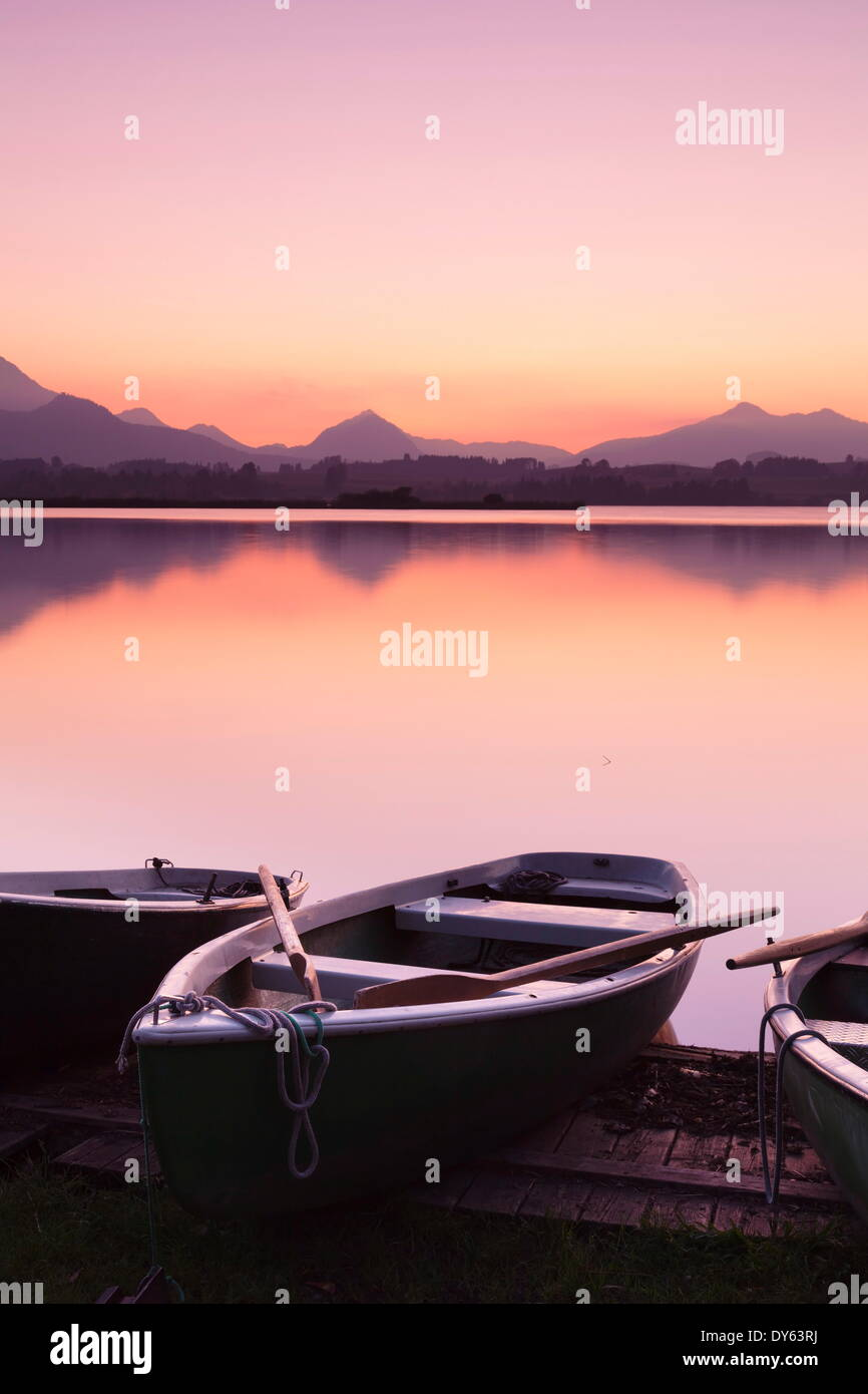 Rowing boats on Hopfensee Lake at sunset, near Fussen, Allgau, Allgau Alps, Bavaria, Germany, Europe - Stock Image