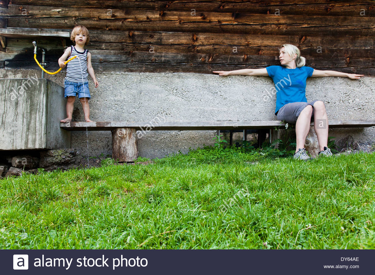 Woman and child on a bench infront of a farmhouse, Kloaschau Valley, Bayrischzell, Bavaria, Germany - Stock Image