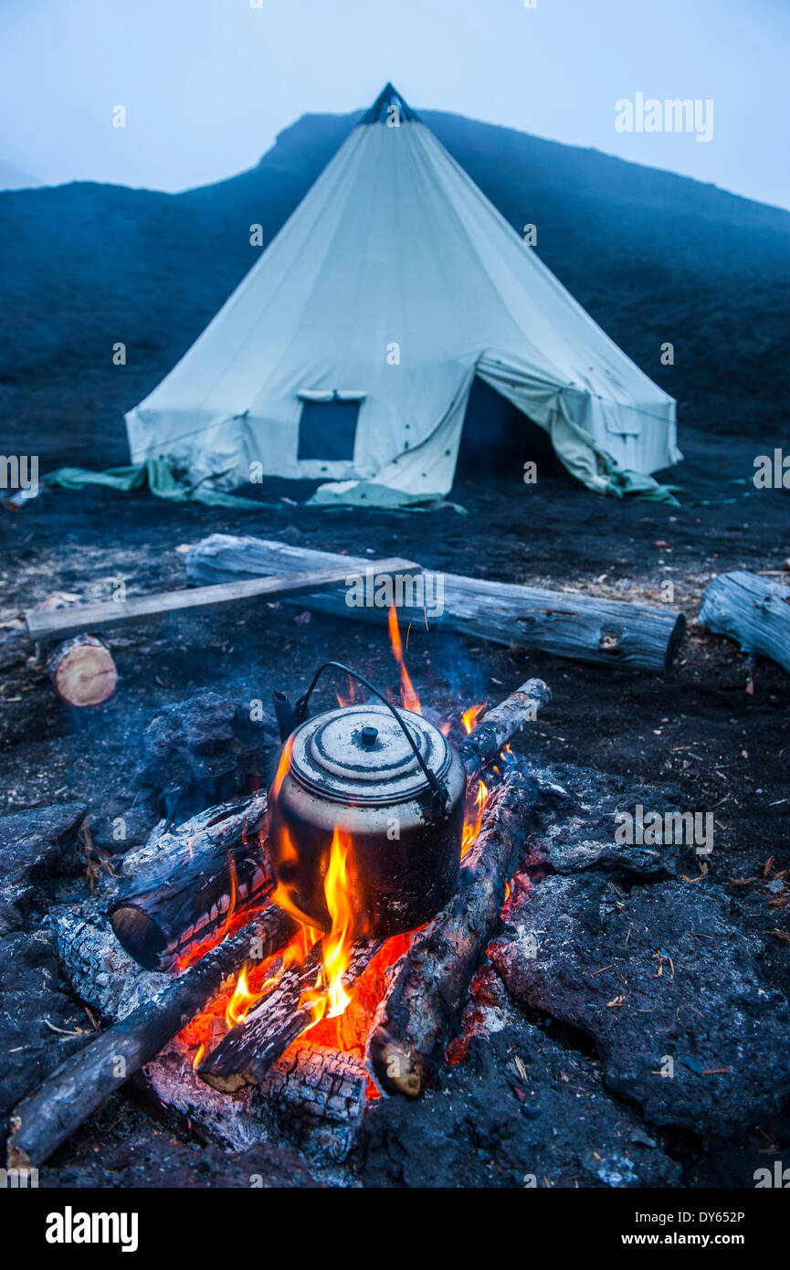 Boiling water pot over an open fire on a campsite and tipi on Tolbachik volcano, Kamchatka, Russia, Eurasia - Stock Image