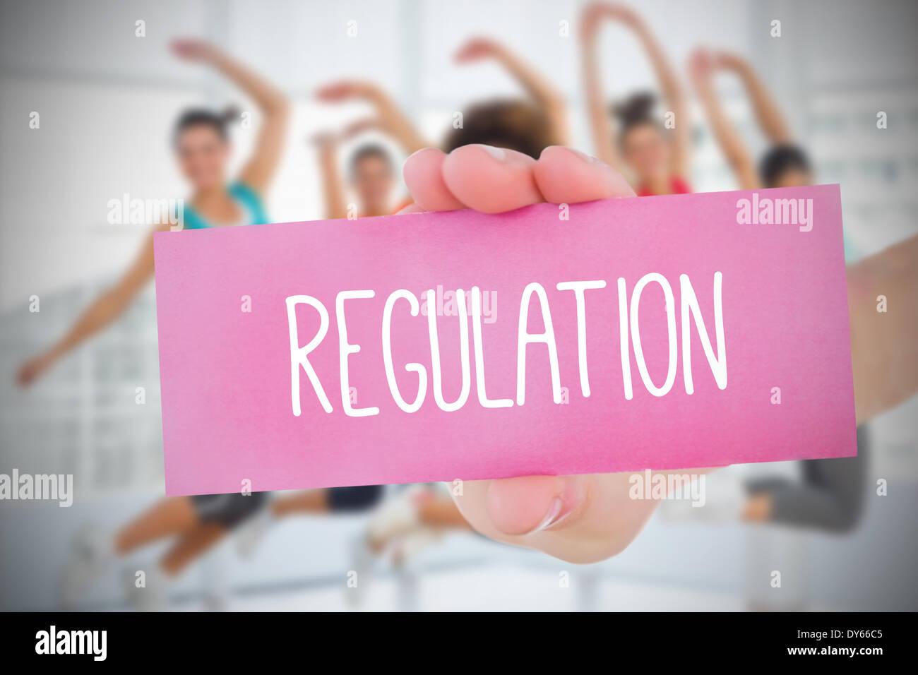 Woman holding pink card saying regulation - Stock Image
