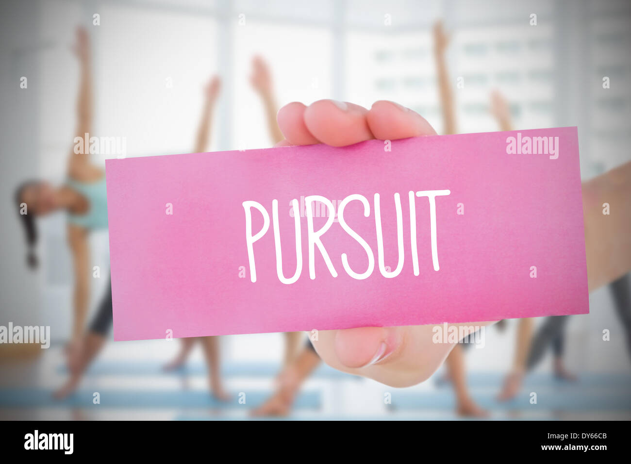 Woman holding pink card saying pursuit - Stock Image