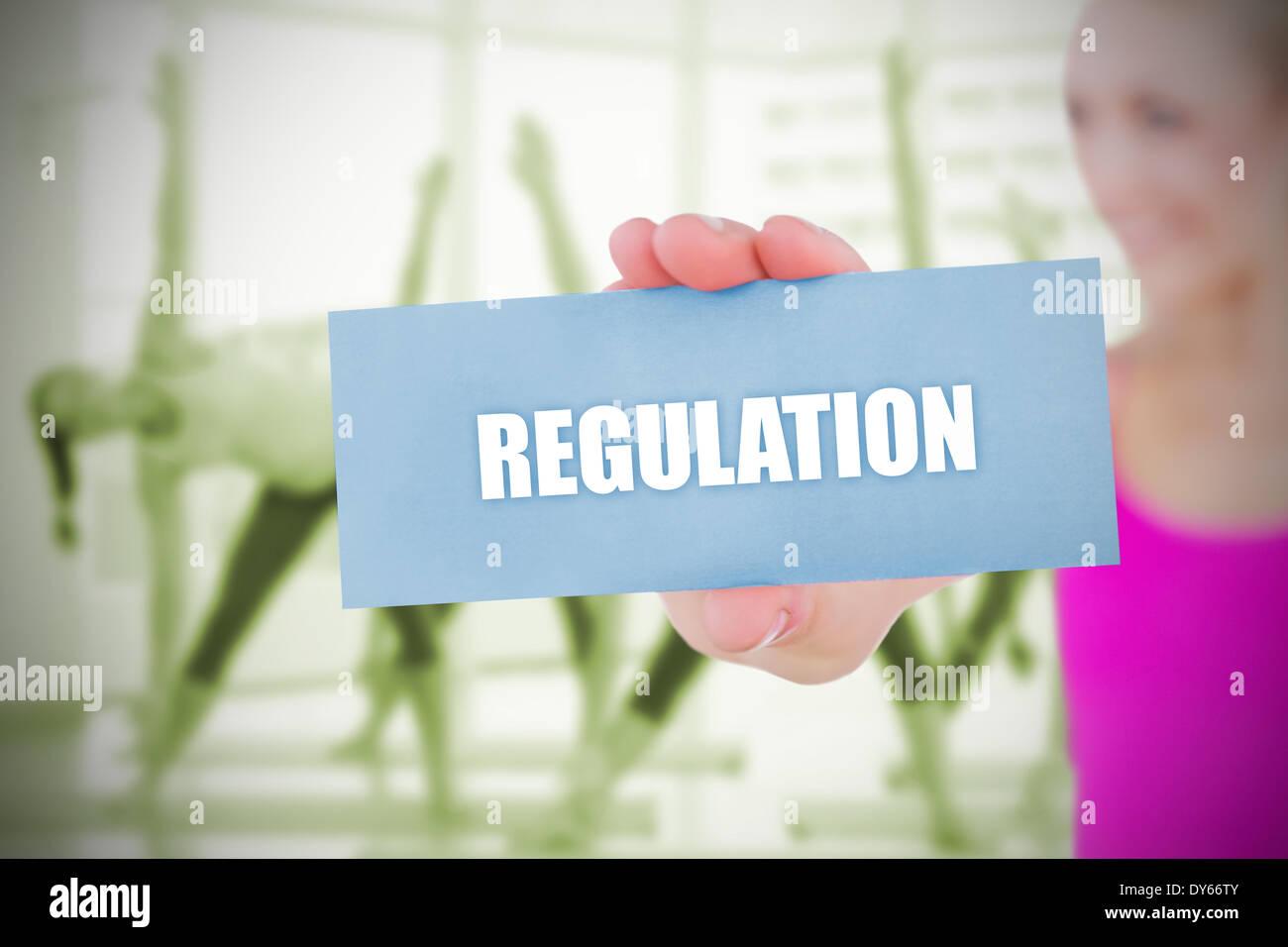 Fit blonde holding card saying regulation - Stock Image