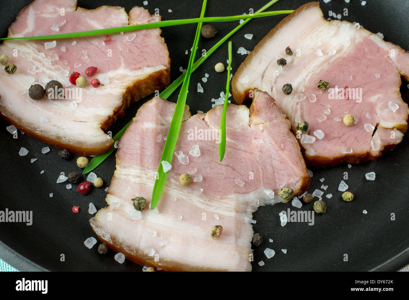 Pieces of bacon on a black frying pan with spices, salt and herbs. - Stock Image
