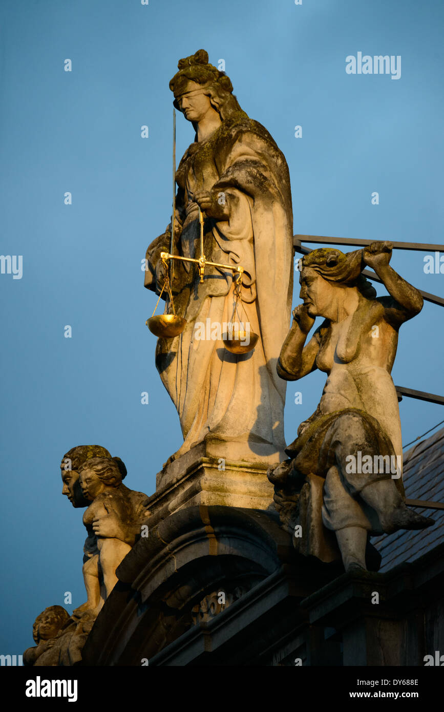BRUGES, Belgium - The early morning light catches a statue of Justice on top of the Provost's House (Proosdij), a historic baroque building dating to 1666 on Burg Square and standing opposite the gothic City Hall (Stadhuis) building. The Provost's House was used as the residence of the bishop of Bruges and now houses the government offices of West Flanders province. - Stock Image