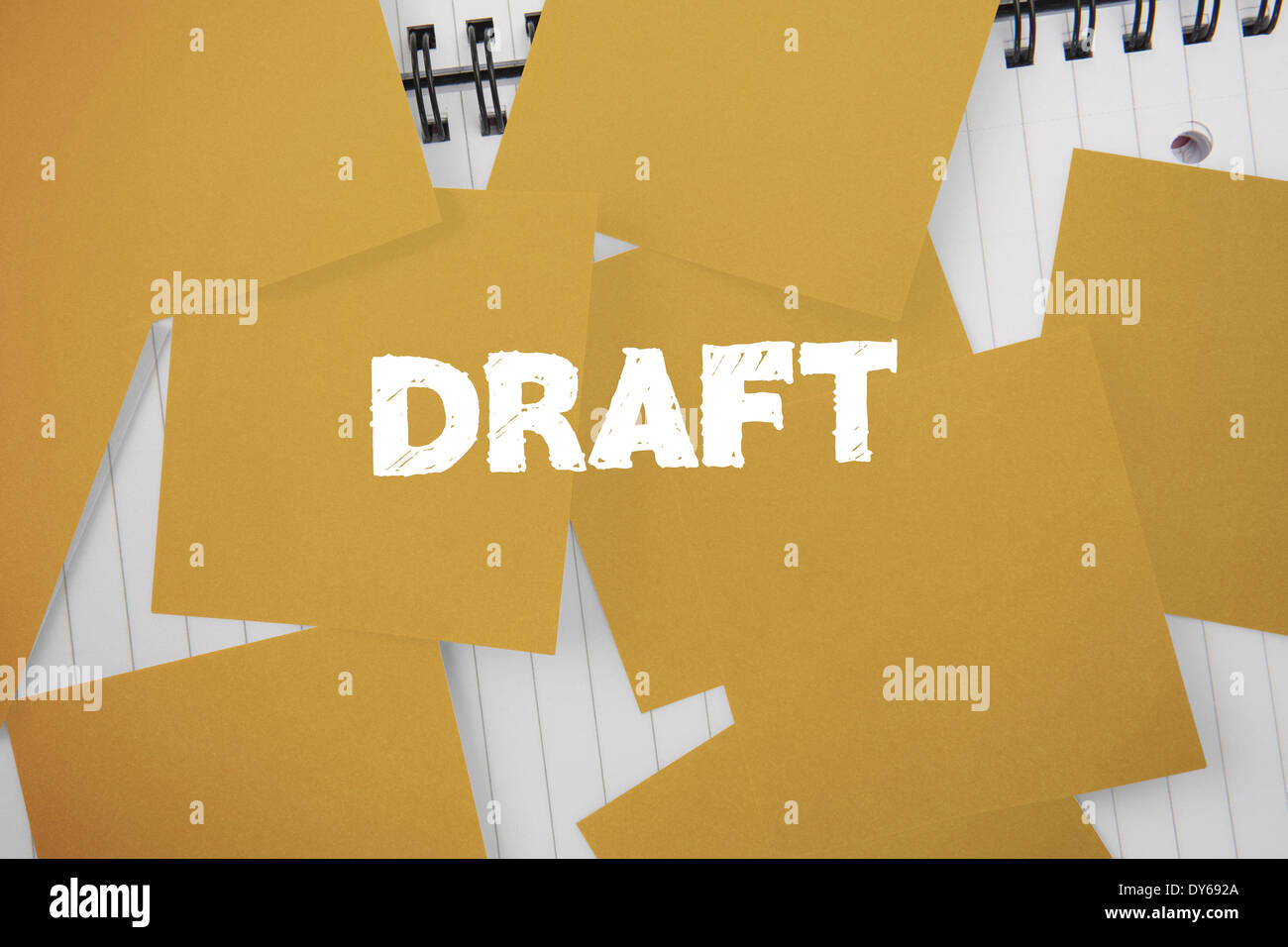 Draft against yellow paper strewn over notepad - Stock Image