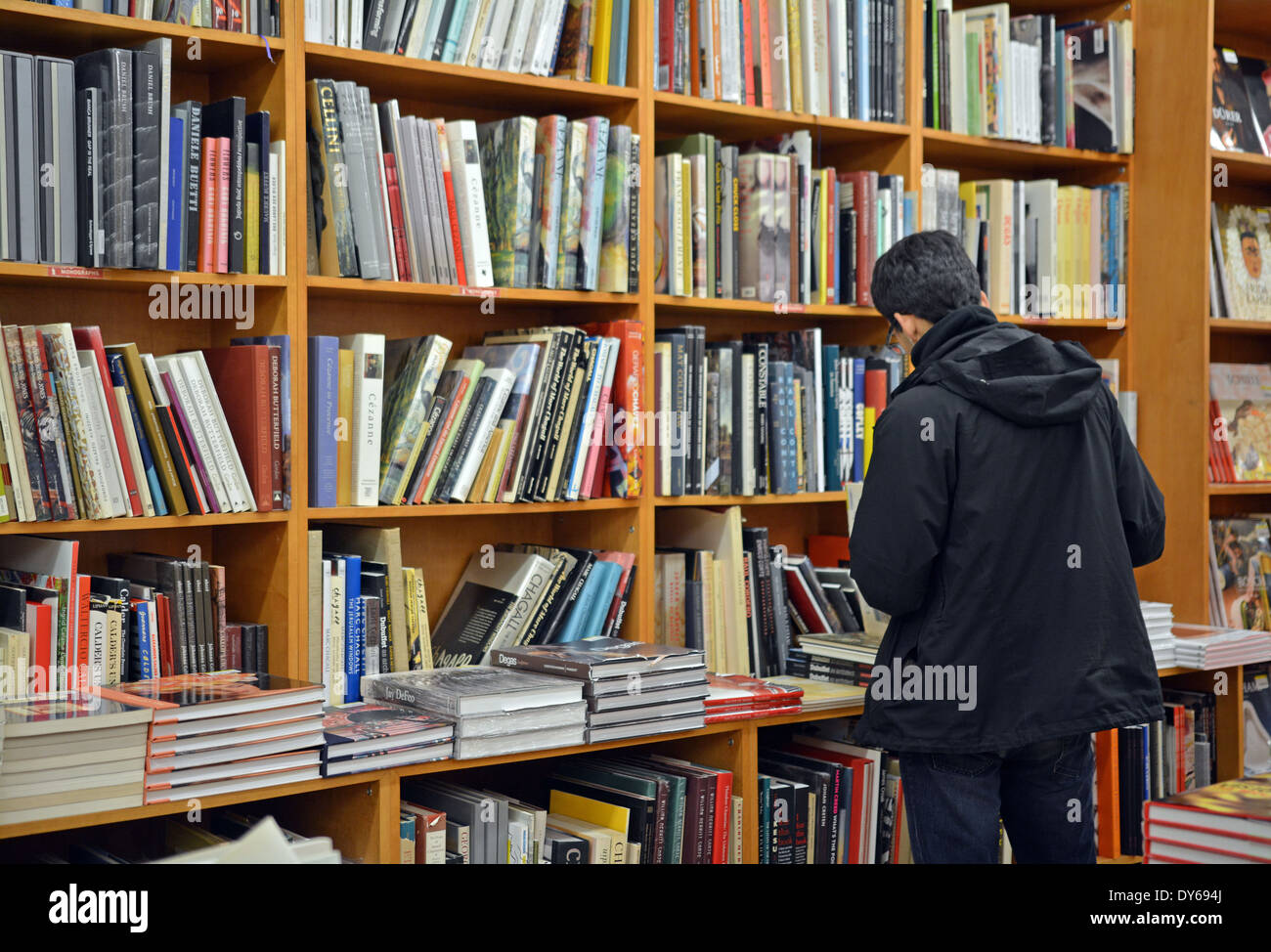 A man in a coat shopping for books at the Strand Bookstore on Broadway in Greenwich Village, Manhattan, NYC. - Stock Image