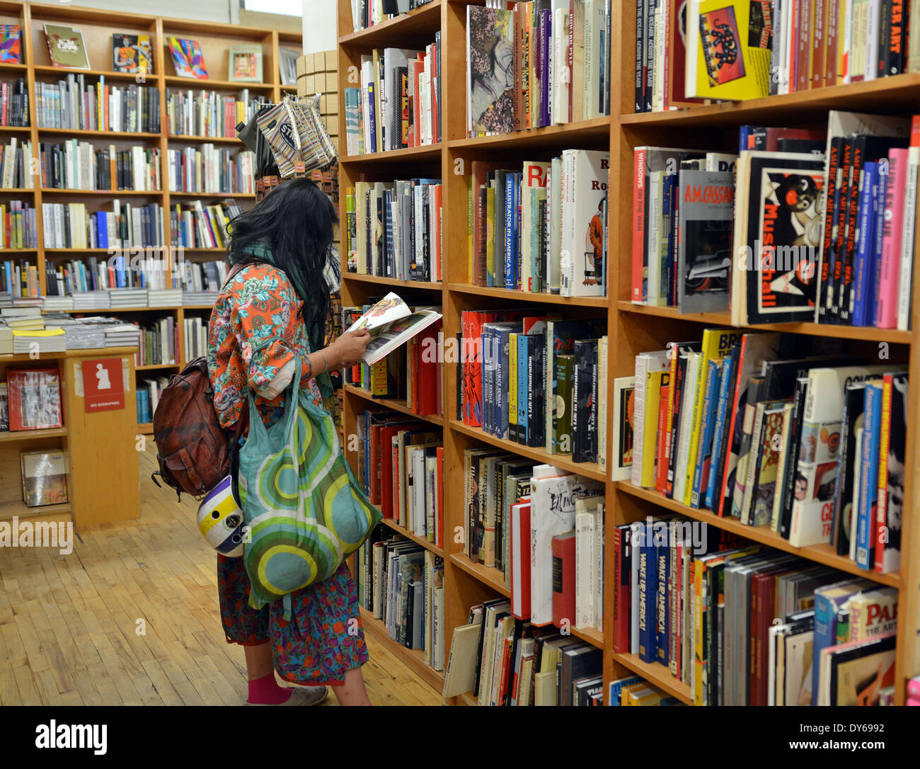 A woman in colorful clothing shopping for books at the Strand Bookstore on Broadway in Greenwich Village, Manhattan, - Stock Image