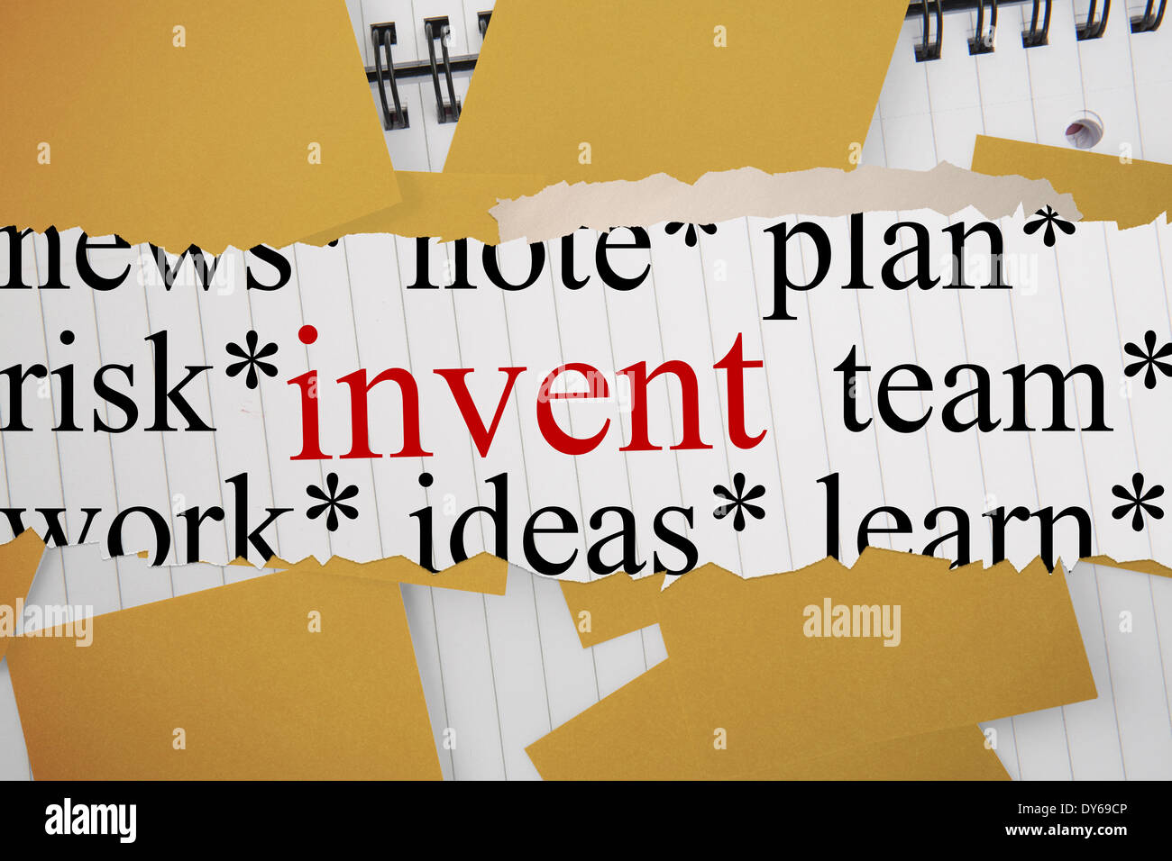 Invent against yellow paper strewn over notepad - Stock Image