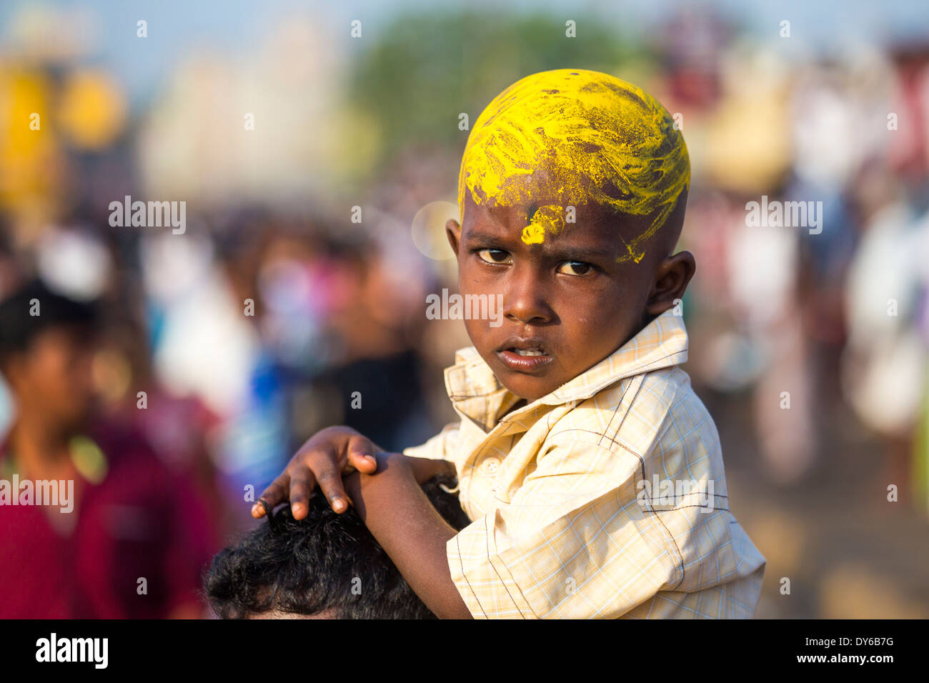 Boy rides on shoulders during Chithirai Thiruvizha Hindu Festival, Madurai, India - Stock Image