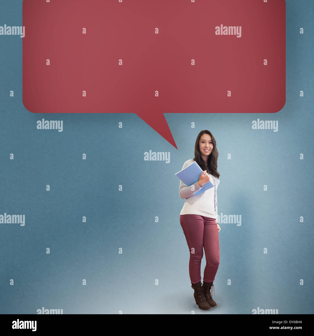 Composite image of smiling student holding textbook with speech bubble - Stock Image