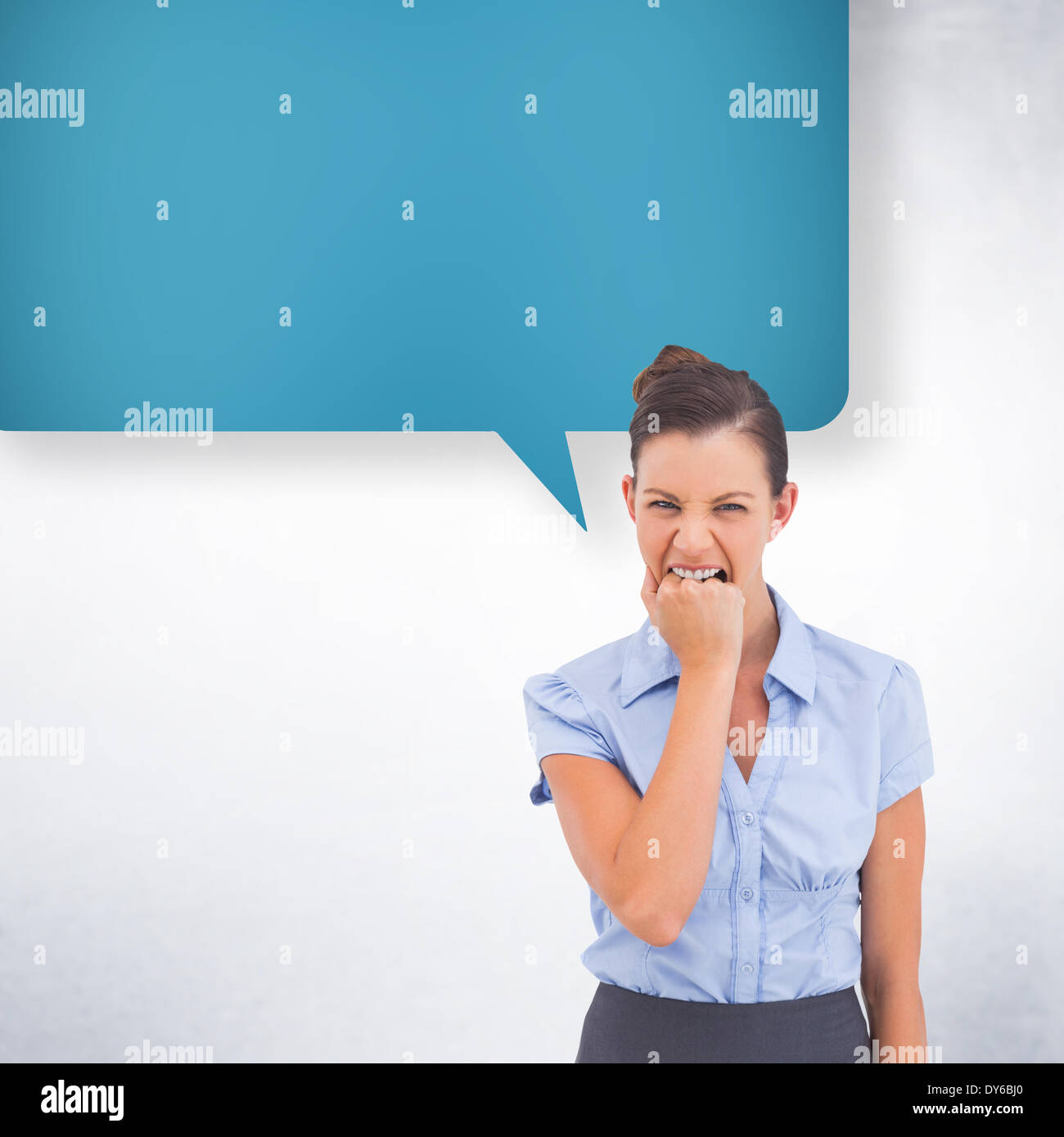 Composite image of furious businesswoman with speech bubble looking at the camera - Stock Image