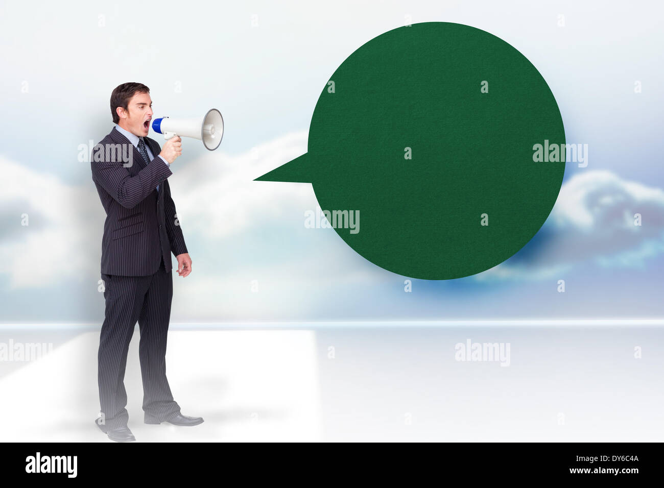 Composite image of standing businessman shouting through a megaphone with speech bubble Stock Photo
