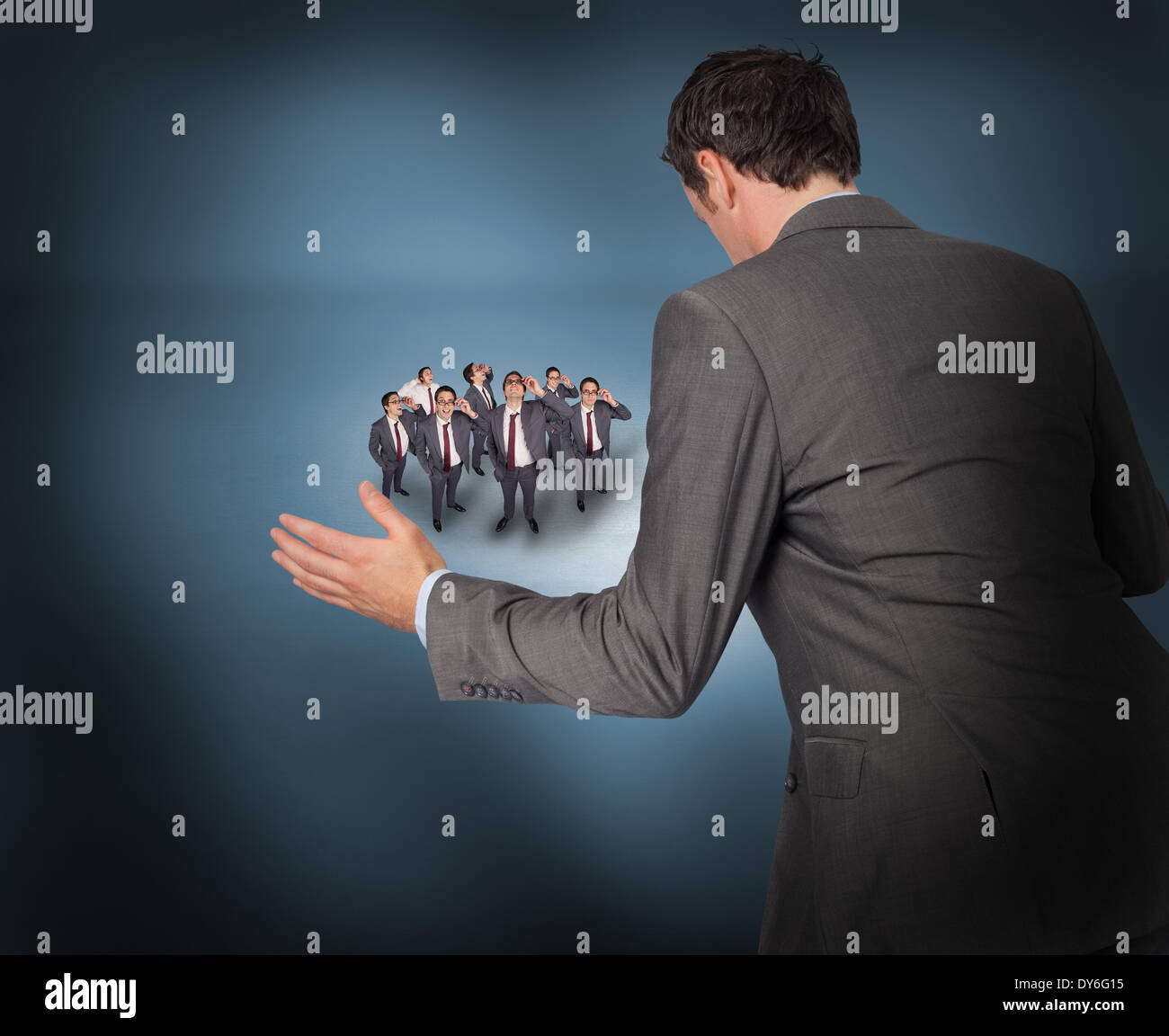 Composite image of businessman posing with hands out with tiny businessmen - Stock Image